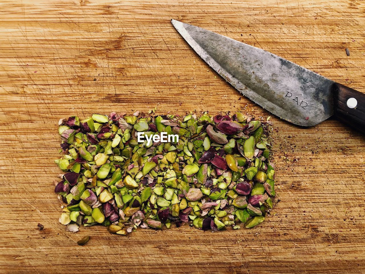 Directly above shot of chopped pistachios by knife on cutting board