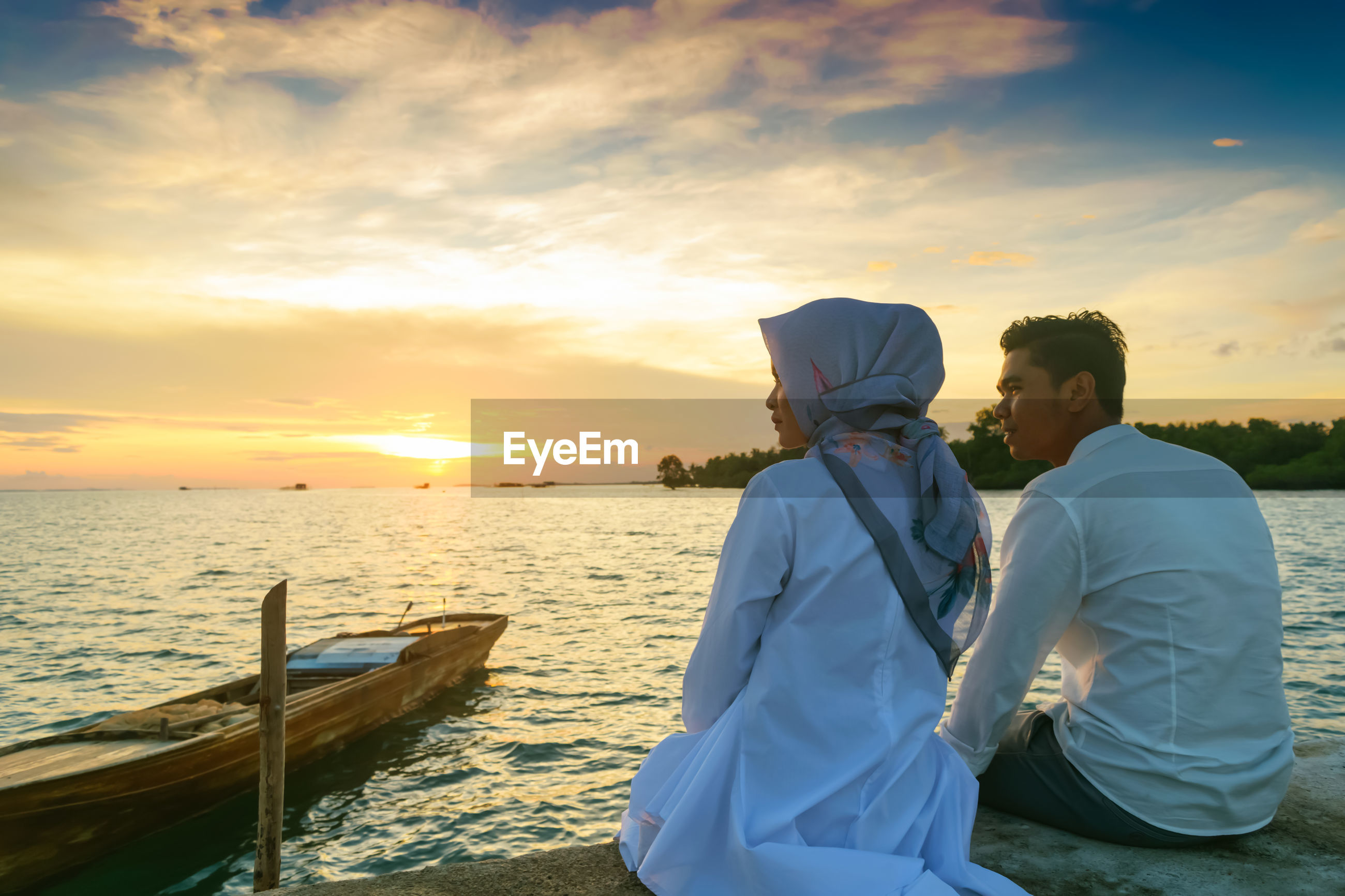 Man and woman looking at sea during sunset