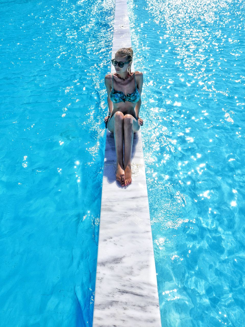 Young woman swimming in pool during summer