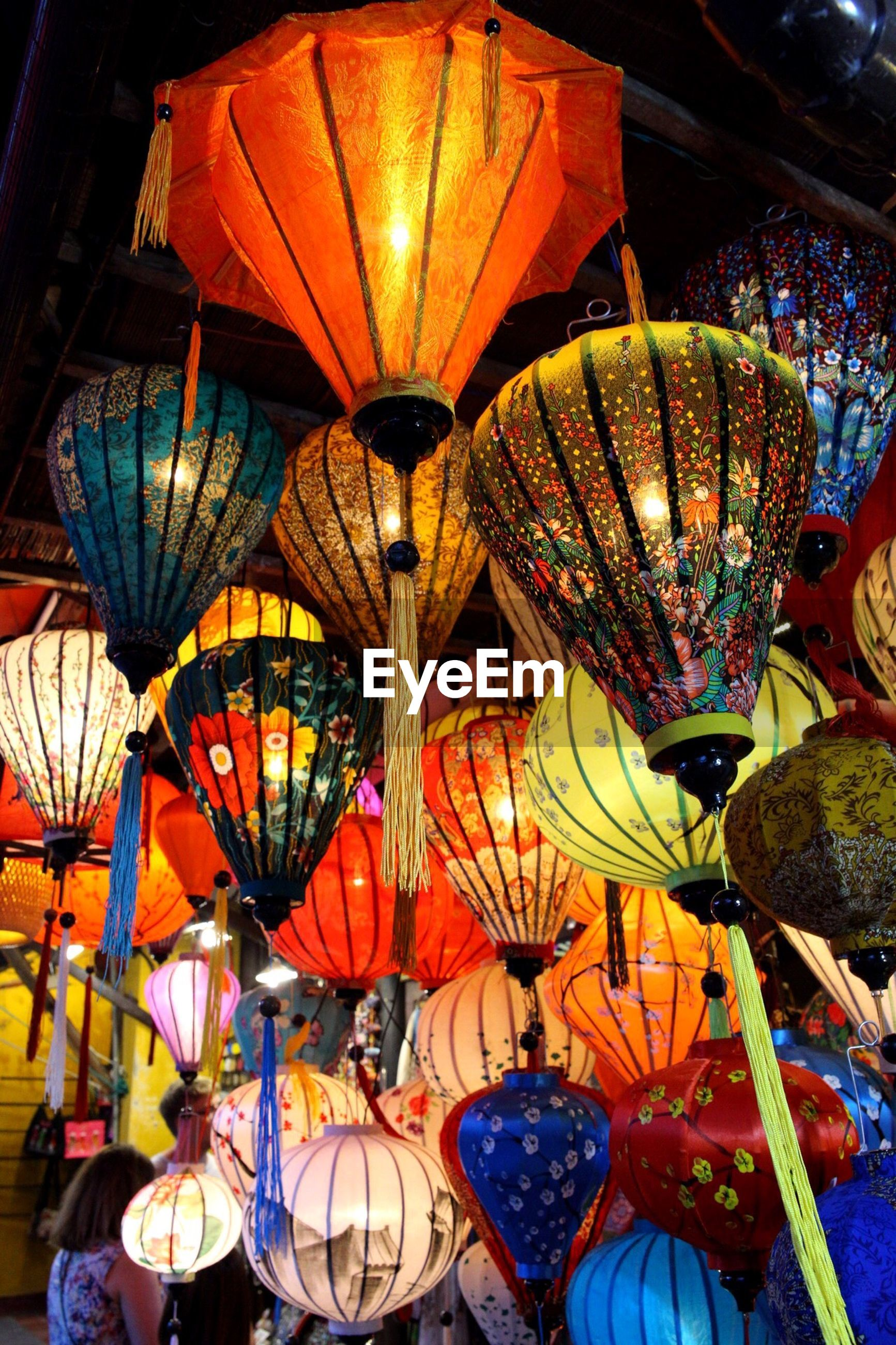 LOW ANGLE VIEW OF LANTERNS HANGING IN MARKET AT NIGHT
