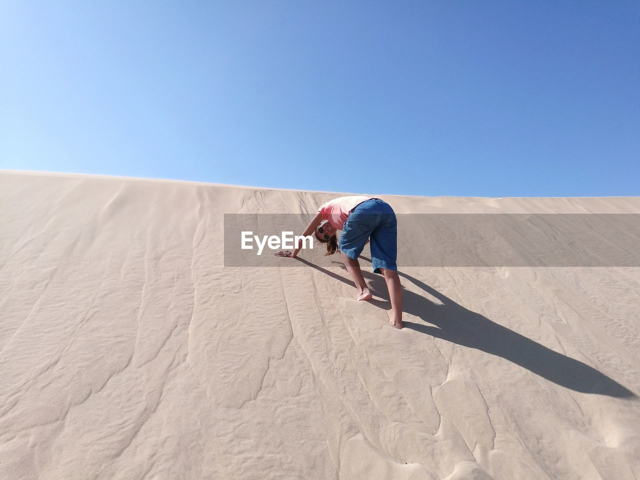 Low angle view of woman on sand dune against clear blue sky