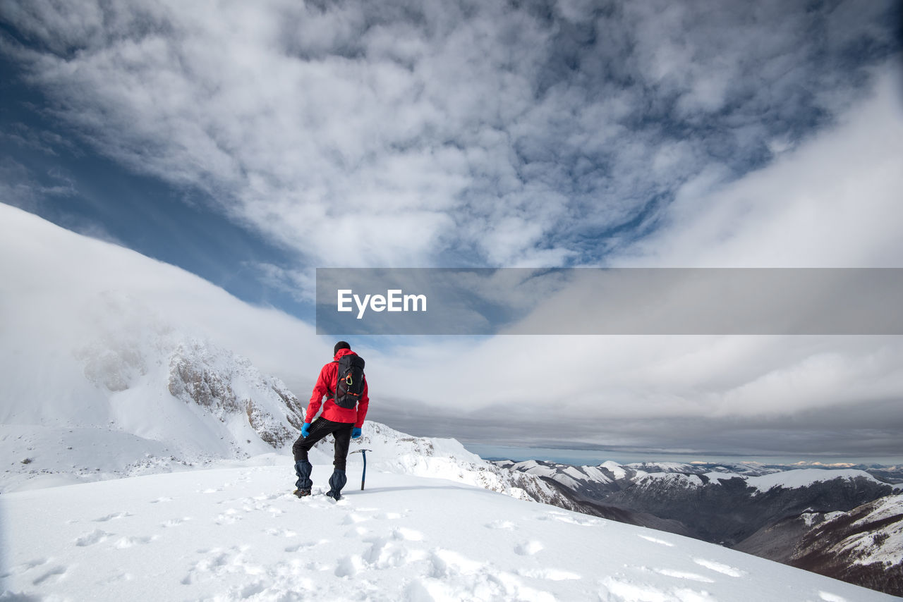 winter, cloud - sky, snow, cold temperature, leisure activity, sky, mountain, beauty in nature, scenics - nature, adventure, rear view, lifestyles, real people, non-urban scene, nature, clothing, people, full length, white color, warm clothing, mountain range, snowcapped mountain, extreme weather