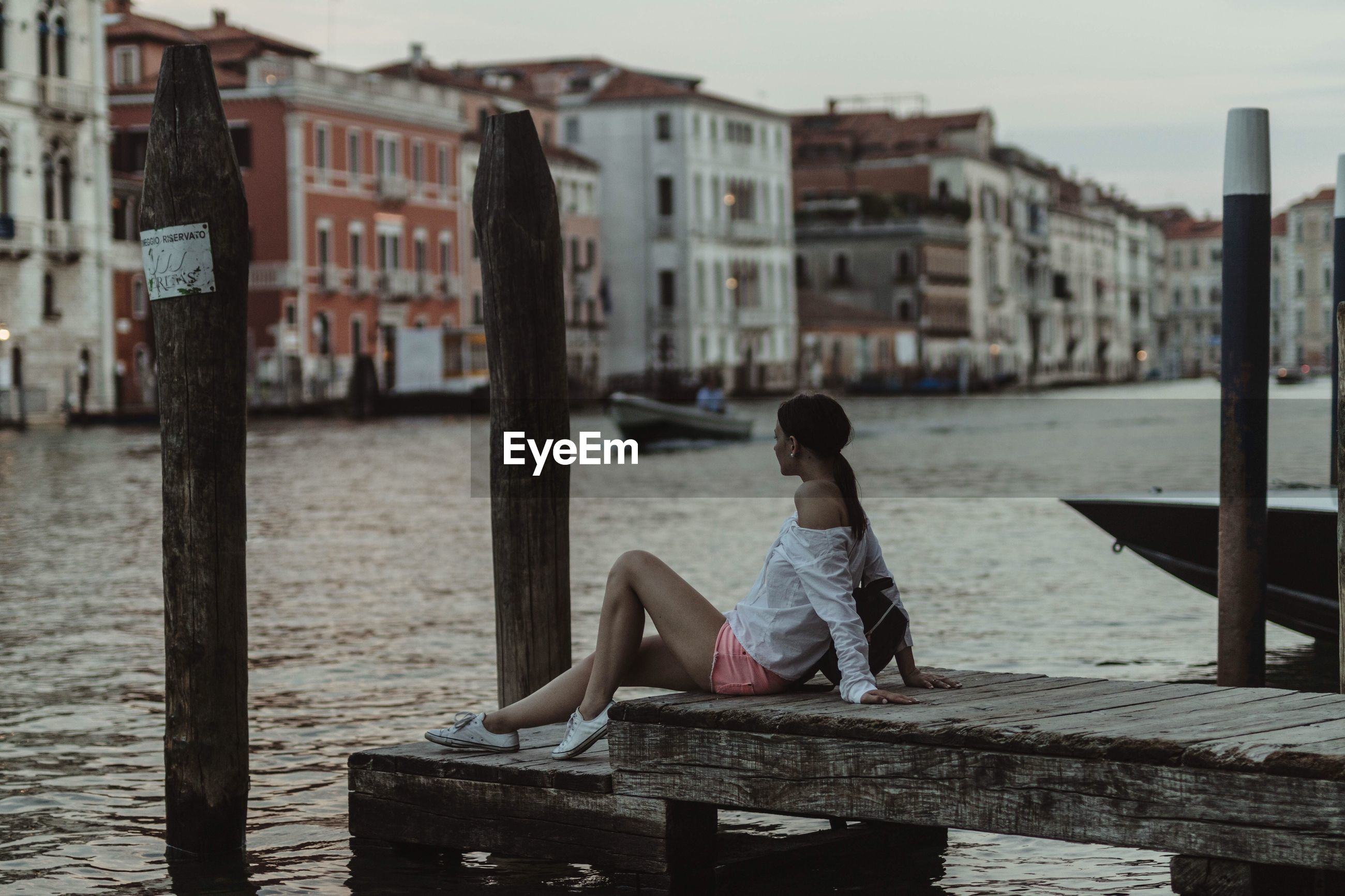 Side view of woman sitting on pier by grand canal during sunset