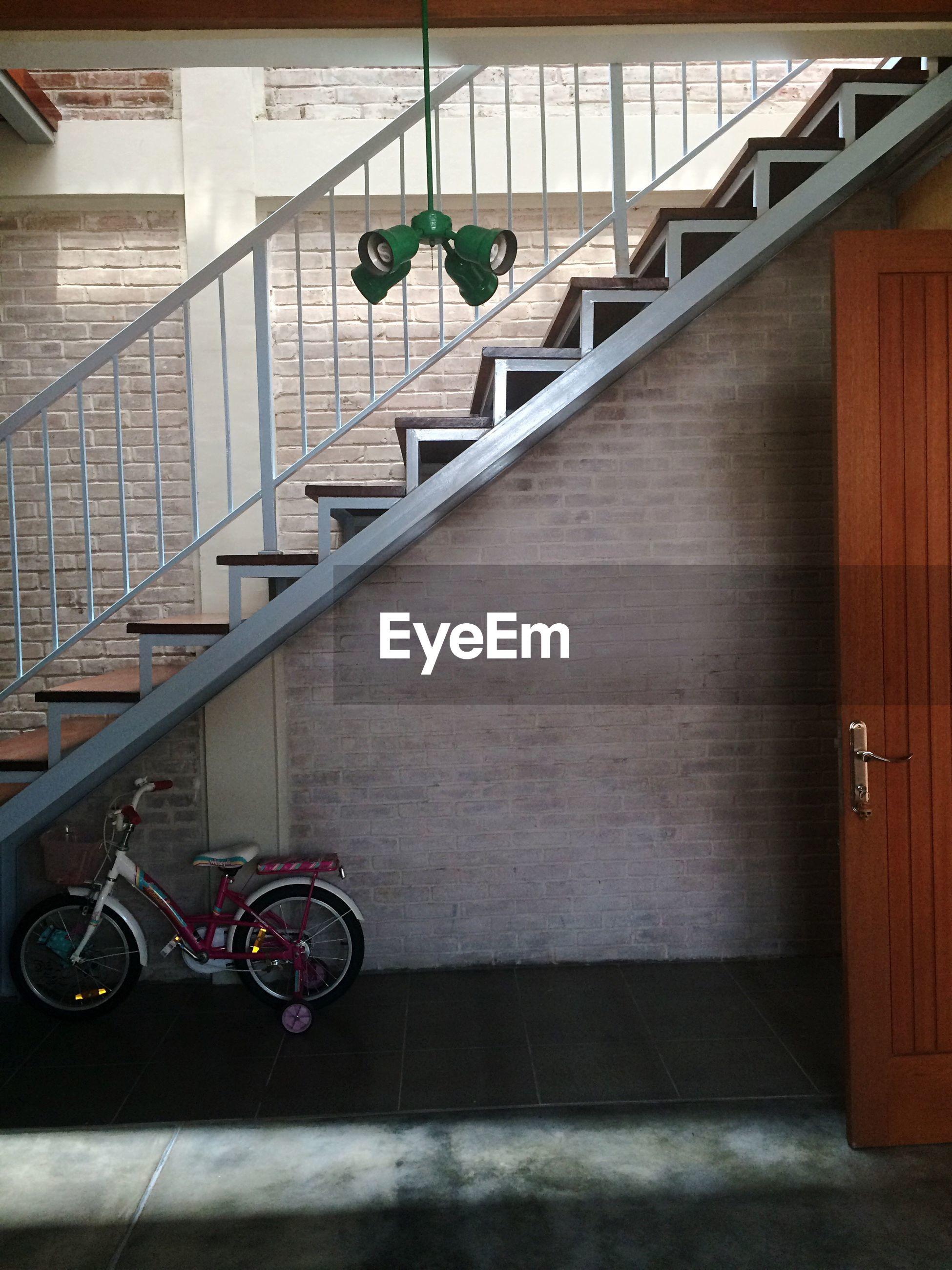 Bicycle below staircase in building