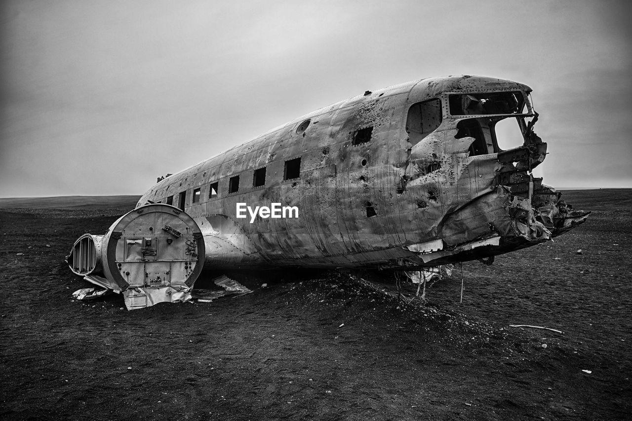 Plane wreck on black beach against sky