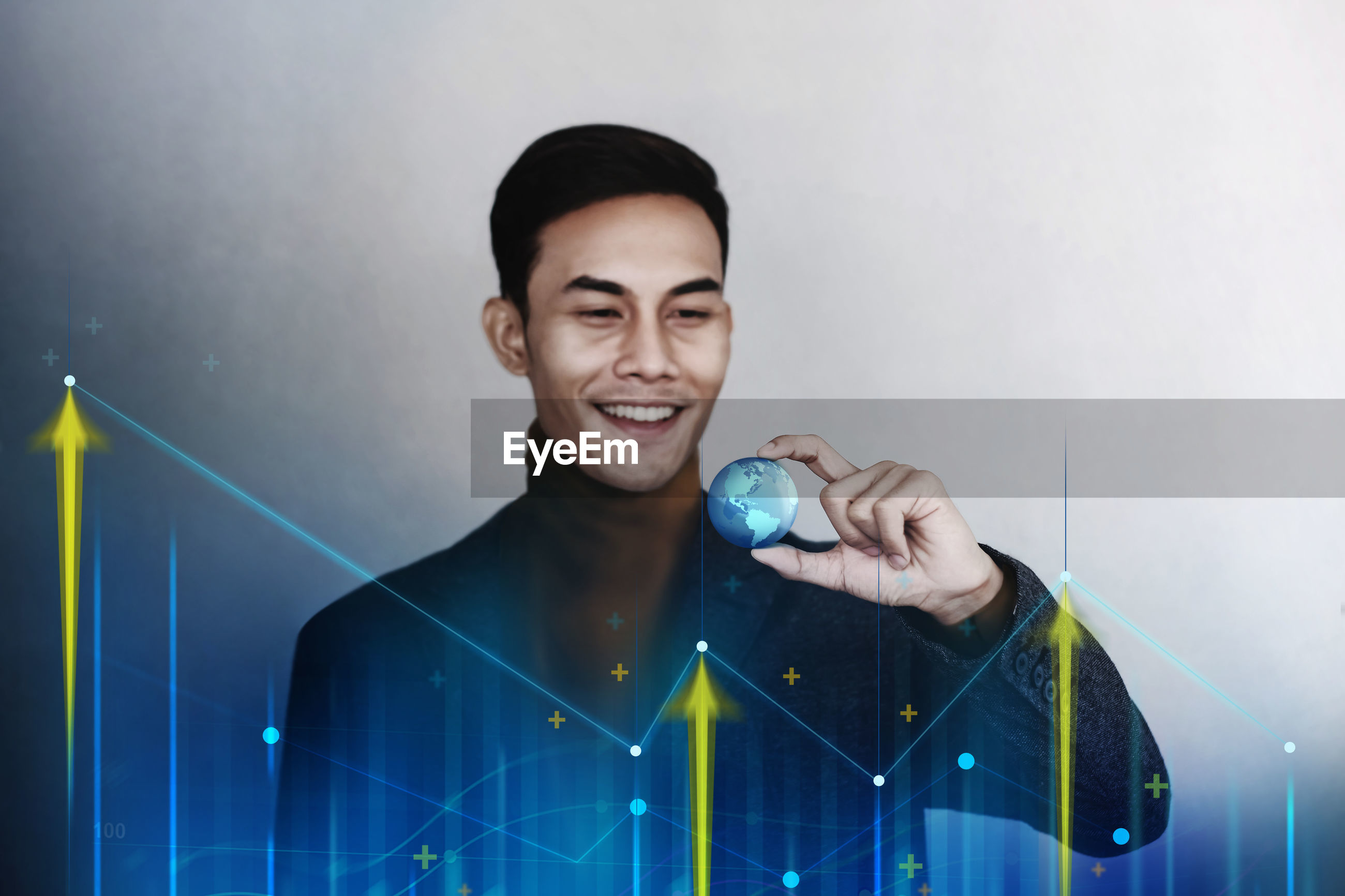Digital composite image of smiling young man holding globe