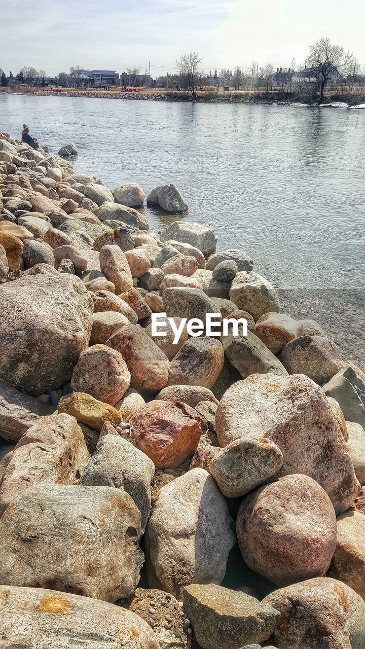 water, pebble, rock - object, nature, day, outdoors, pebble beach, river, no people, riverbank, tranquil scene, tranquility, beauty in nature, beach, sky, tree