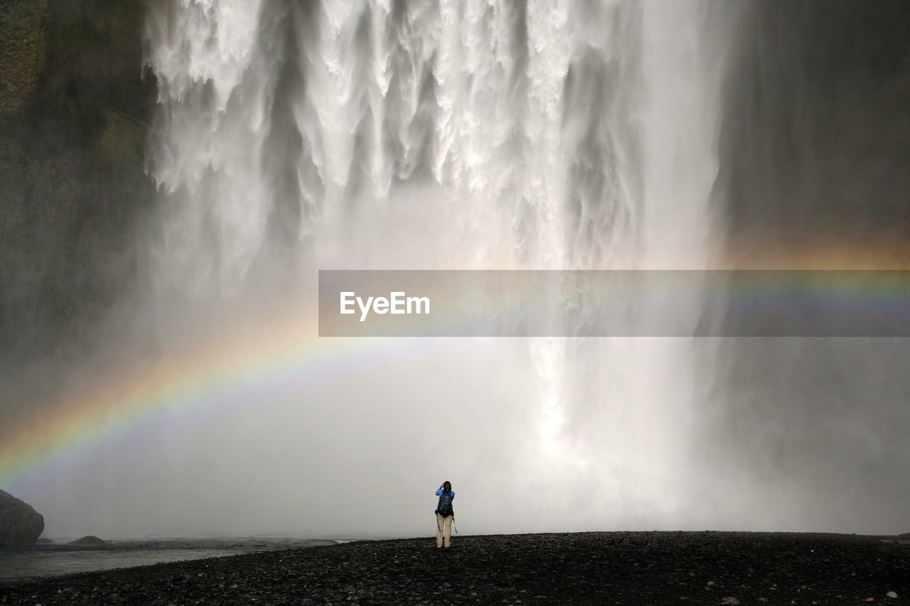 Tourist enjoying the view of waterfall and rainbow