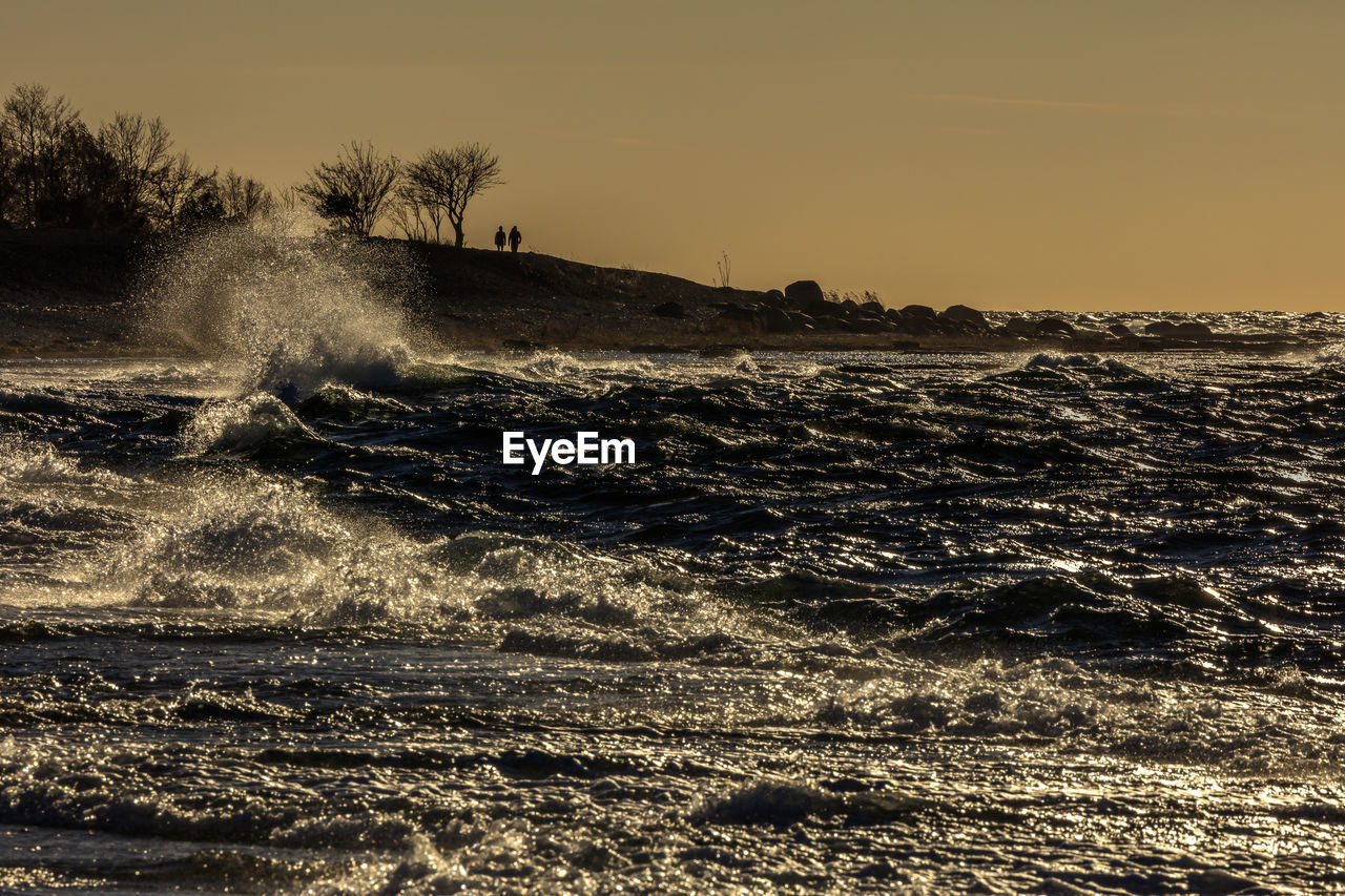 sky, motion, water, sea, beauty in nature, wave, scenics - nature, land, nature, beach, sunset, outdoors, no people, waterfront, clear sky, horizon, splashing, power in nature, sport, horizon over water, flowing water