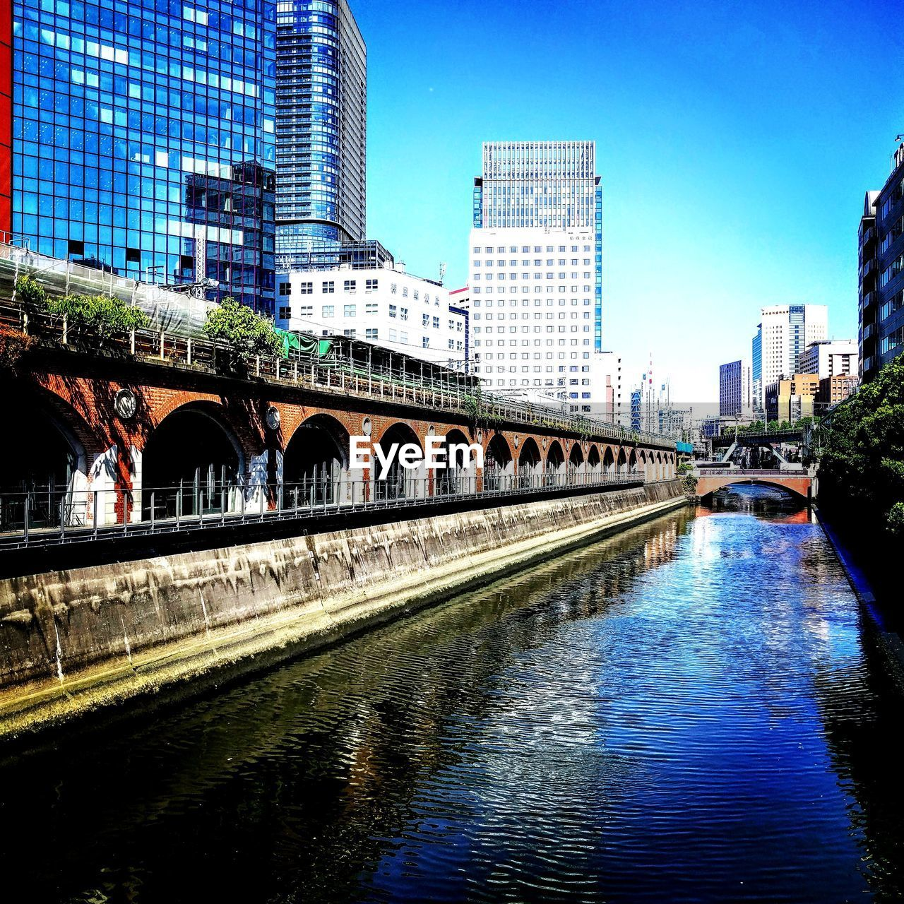 architecture, connection, built structure, bridge - man made structure, city, water, building exterior, reflection, skyscraper, waterfront, modern, blue, river, transportation, outdoors, clear sky, day, sky, no people, cityscape