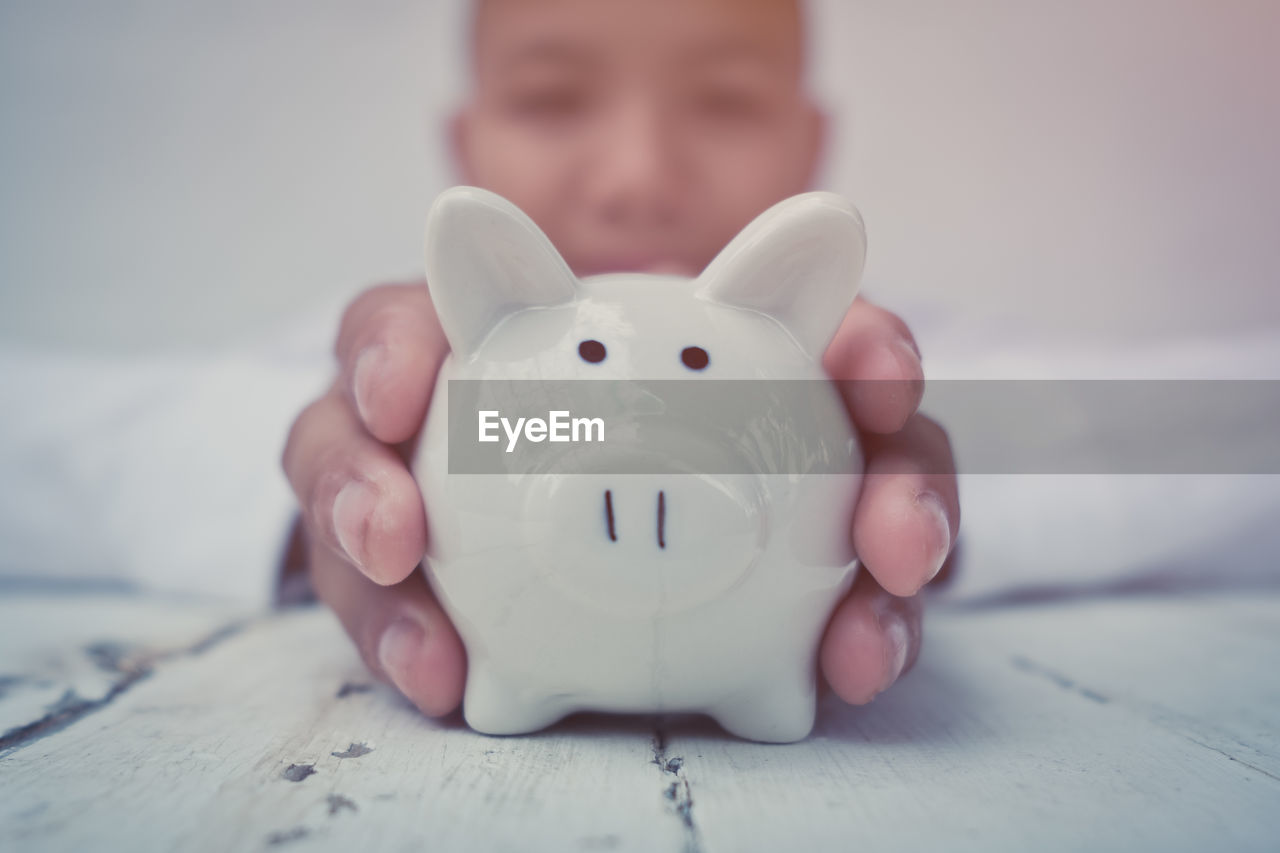 Portrait Of Boy Holding Piggy Bank On Table At Home
