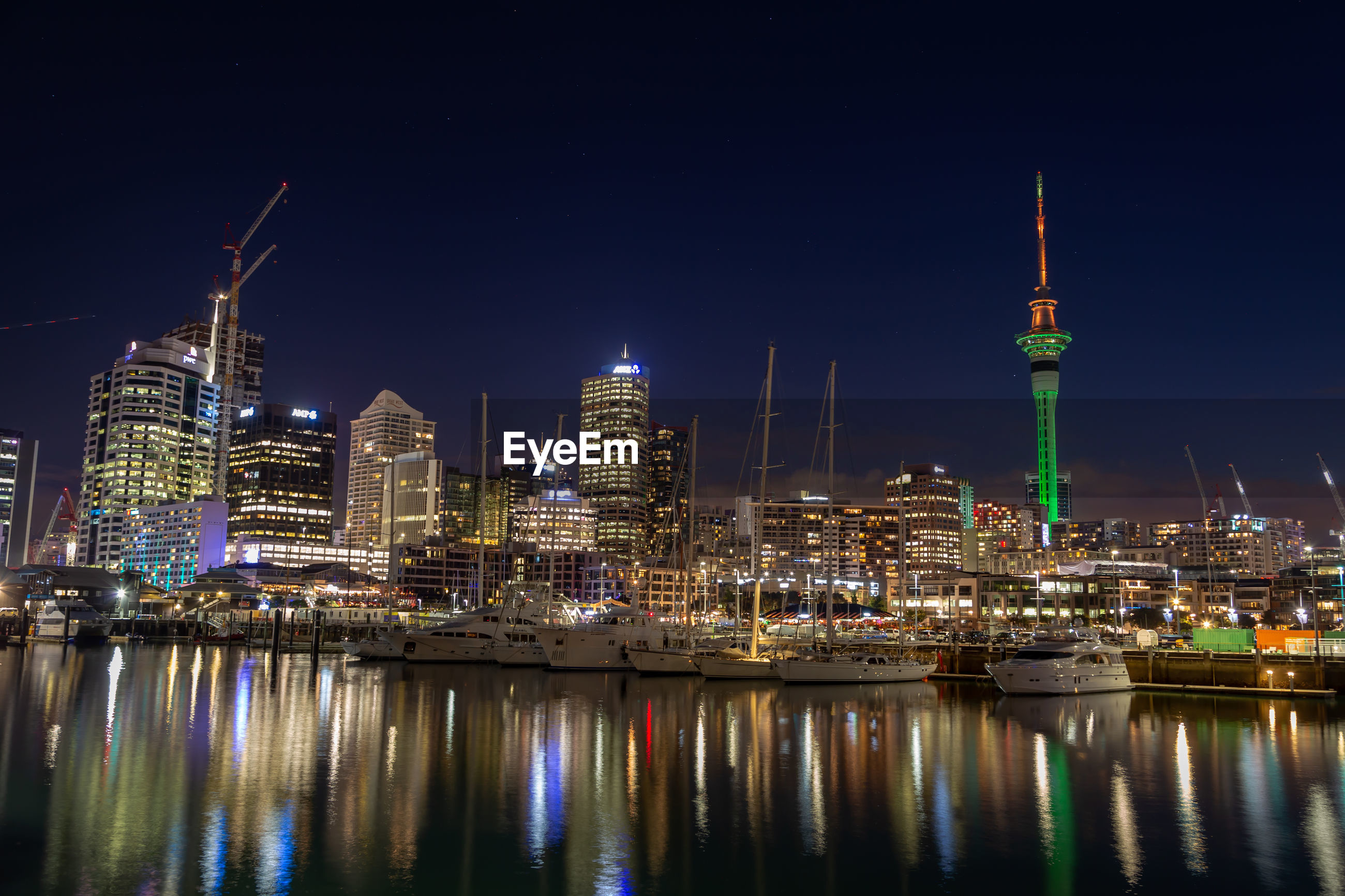 Illuminated city buildings by river at night