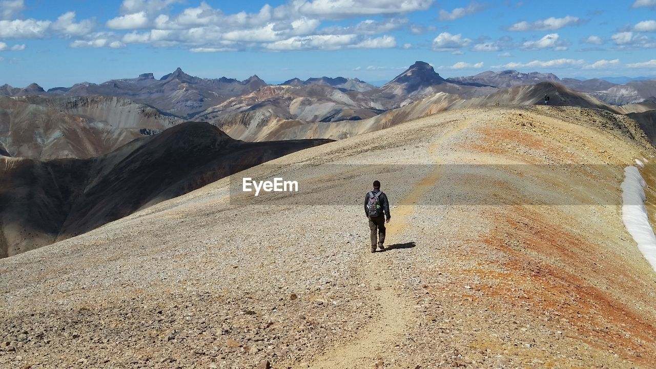 Man walking on landscape against sky