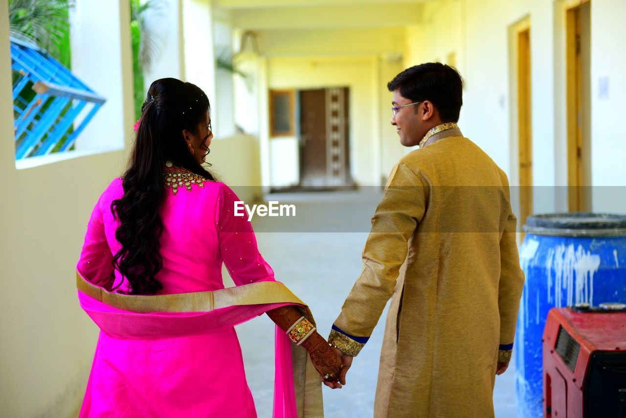 Couple In Traditional Clothing Holding Hands While Walking In Corridor