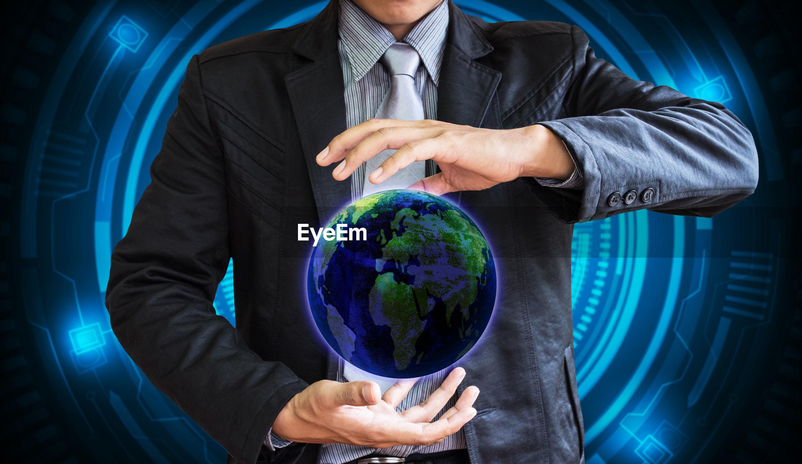 Digital composite image of businessman holding planet earth