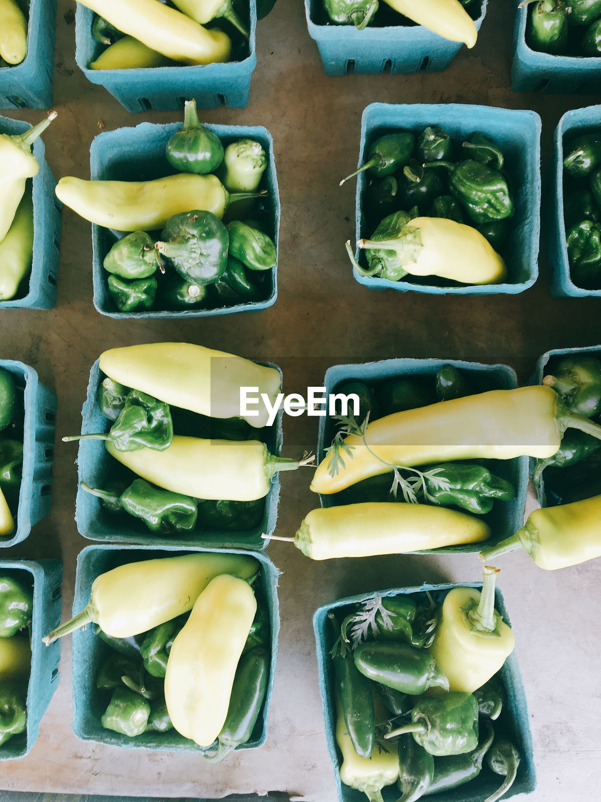 Directly above shot of green peppers in box on table for sale in market