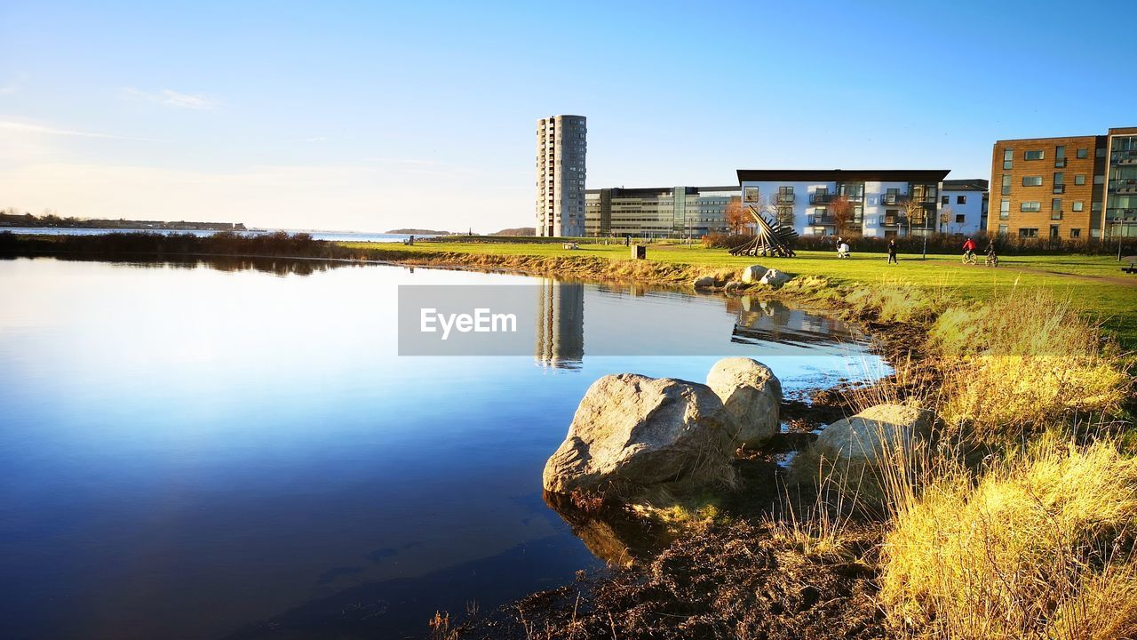 water, building exterior, architecture, built structure, sky, nature, reflection, building, lake, city, no people, day, plant, outdoors, clear sky, waterfront, residential district, grass, office building exterior