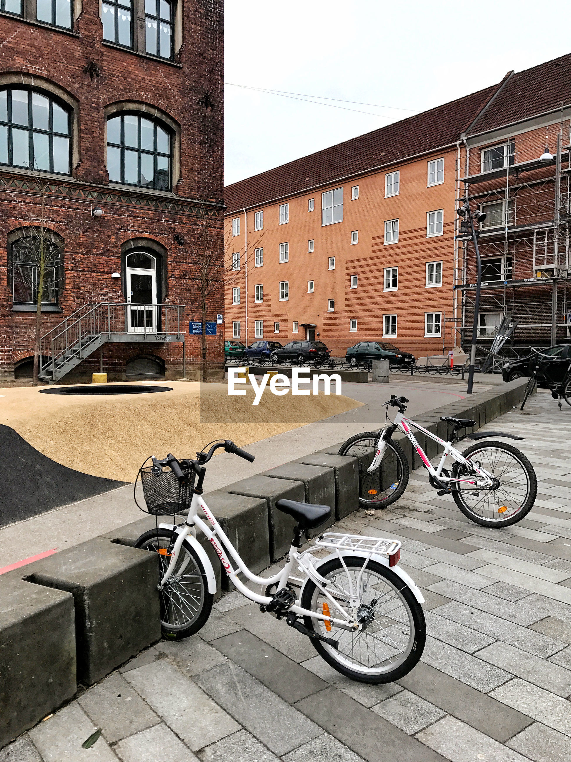 BICYCLES PARKED ON FOOTPATH BY BUILDINGS