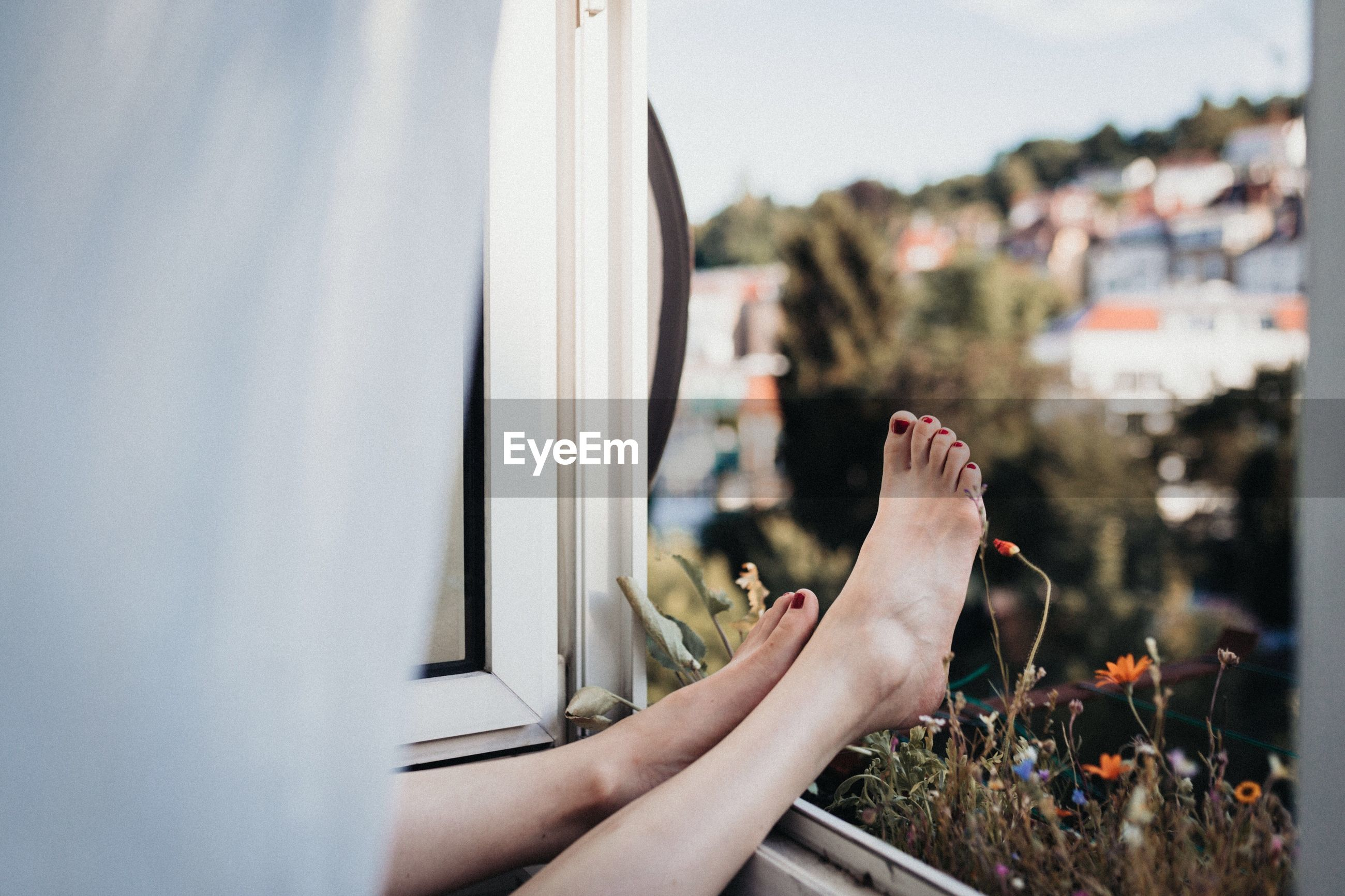 Low section of woman relaxing with legs on window at home