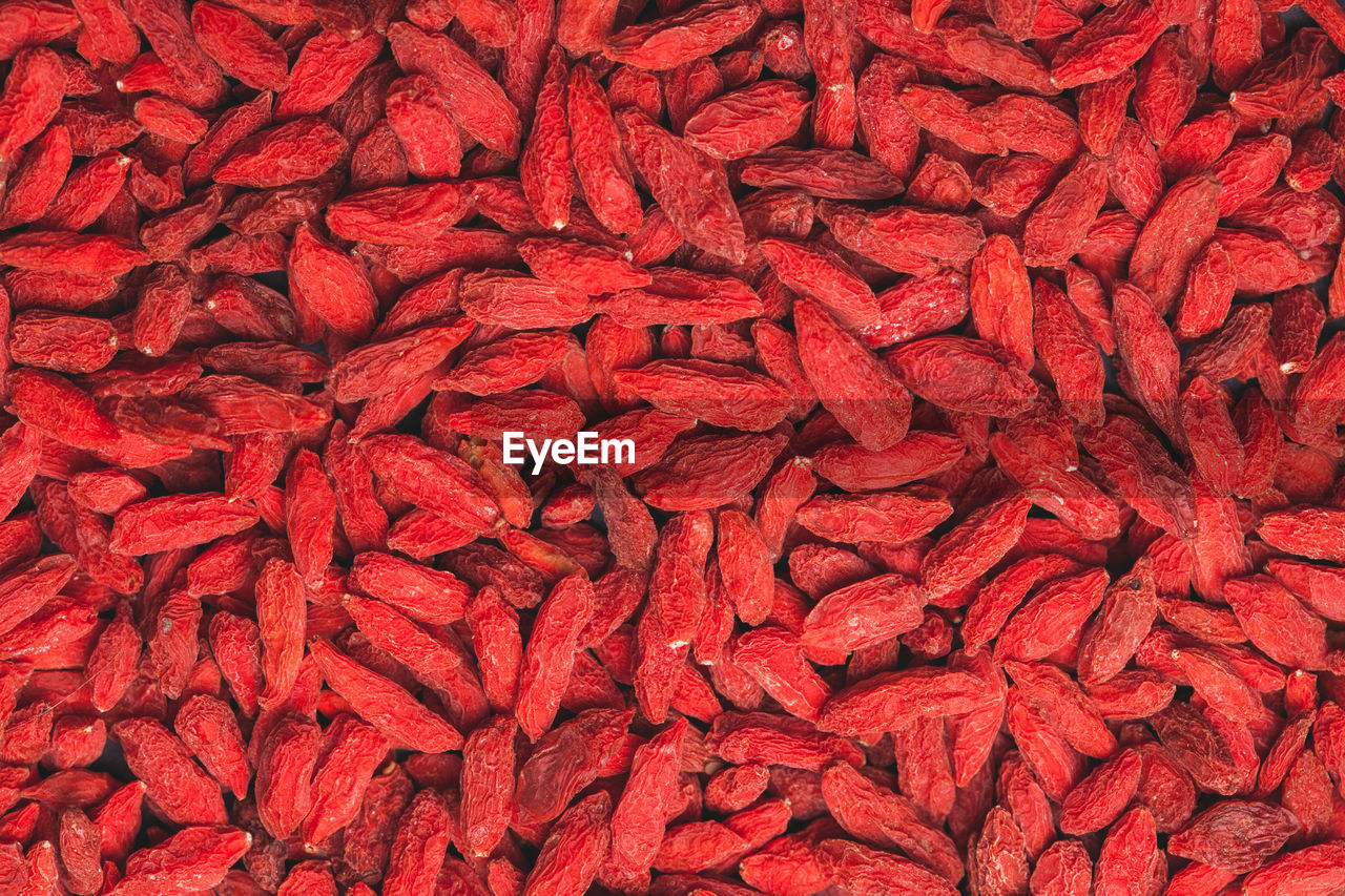 FULL FRAME SHOT OF RED CHILI PEPPER OVER COLORED BACKGROUND
