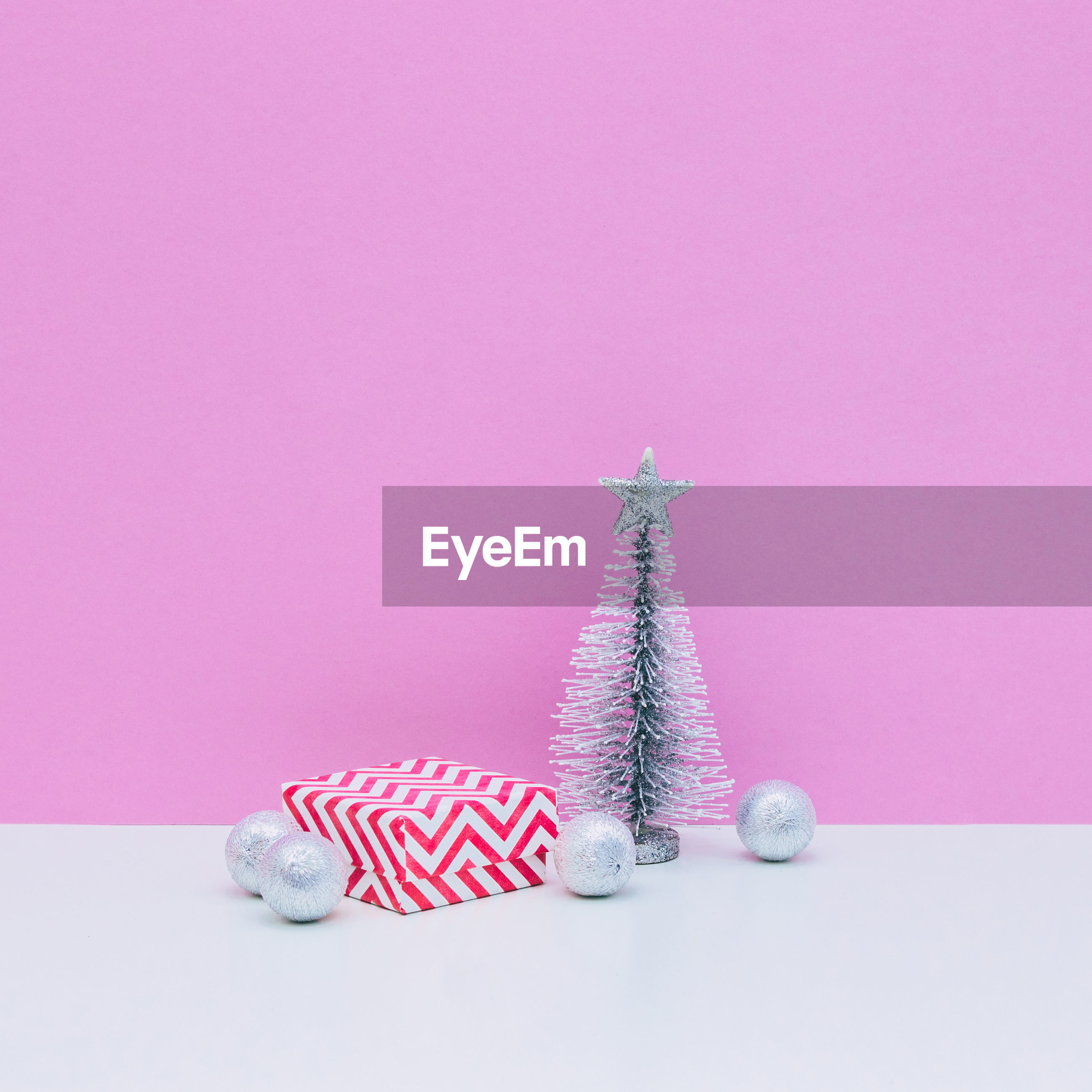 Christmas decoration on table against pink background