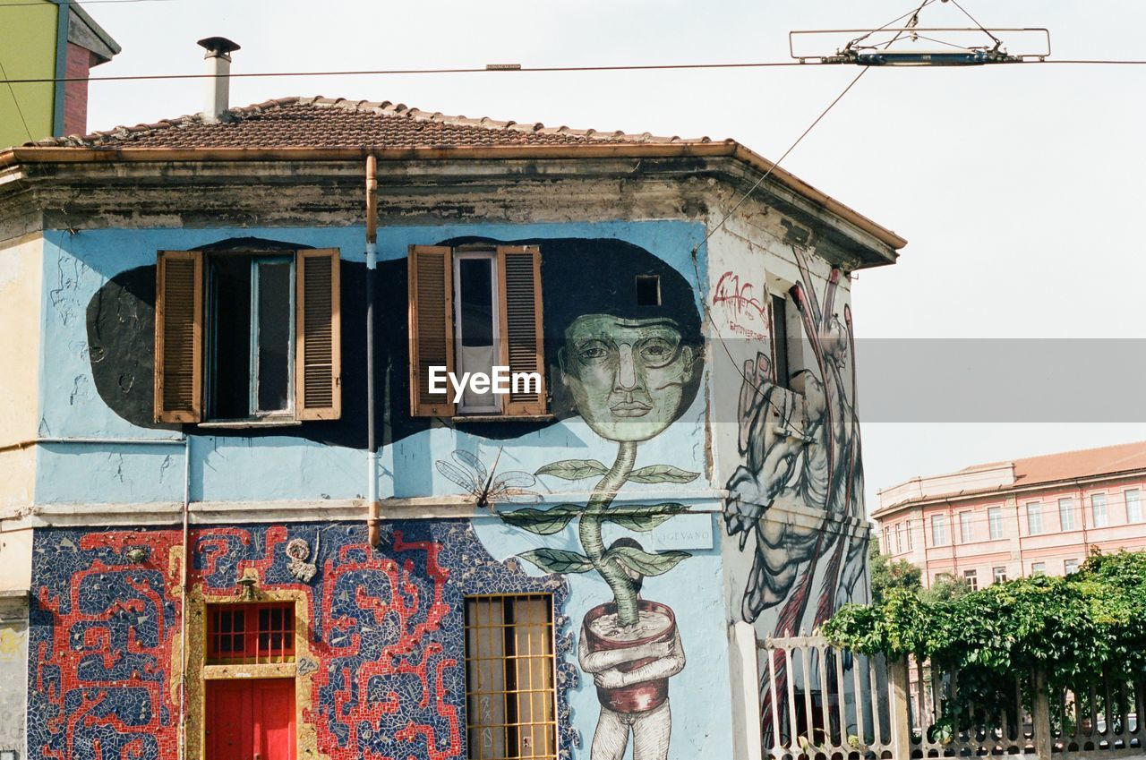 architecture, building exterior, built structure, building, creativity, day, art and craft, representation, no people, sky, nature, human representation, low angle view, clear sky, residential district, outdoors, old, city, house, window, mural, ornate