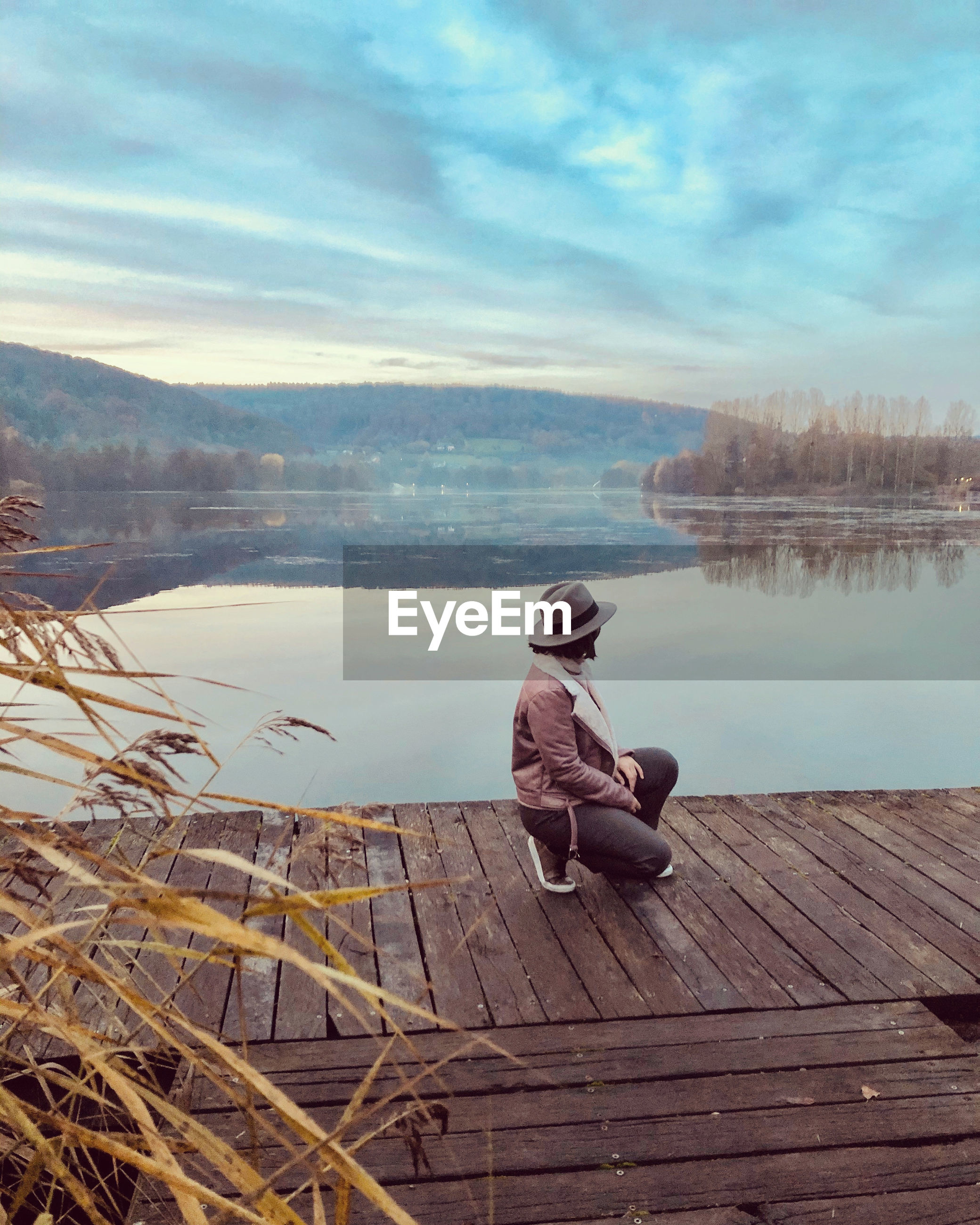 Man by lake on pier