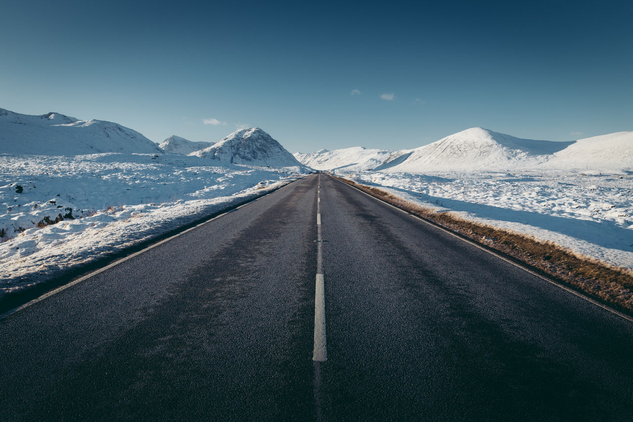 road, direction, the way forward, transportation, diminishing perspective, mountain, cold temperature, snow, tranquil scene, beauty in nature, scenics - nature, sky, winter, tranquility, road marking, vanishing point, no people, symbol, non-urban scene, mountain range, snowcapped mountain, outdoors, dividing line, long