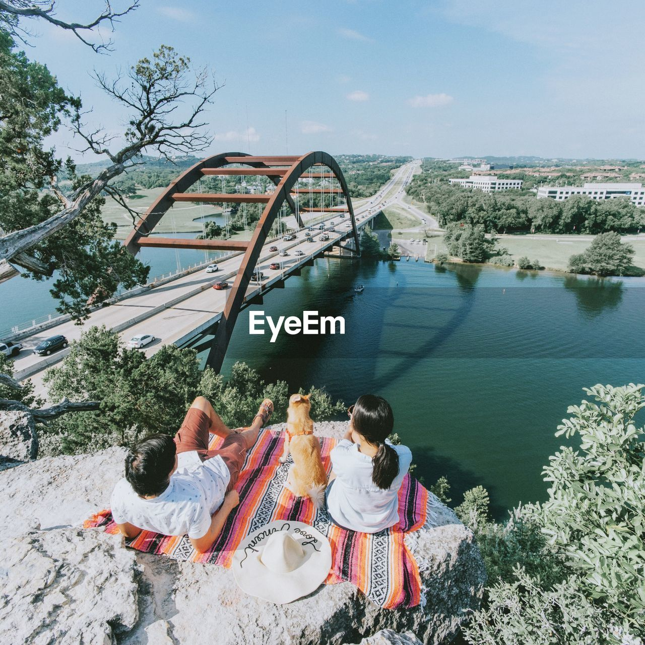 High Angle View Of Couple With Dog Sitting On Cliff By Bridge Over River