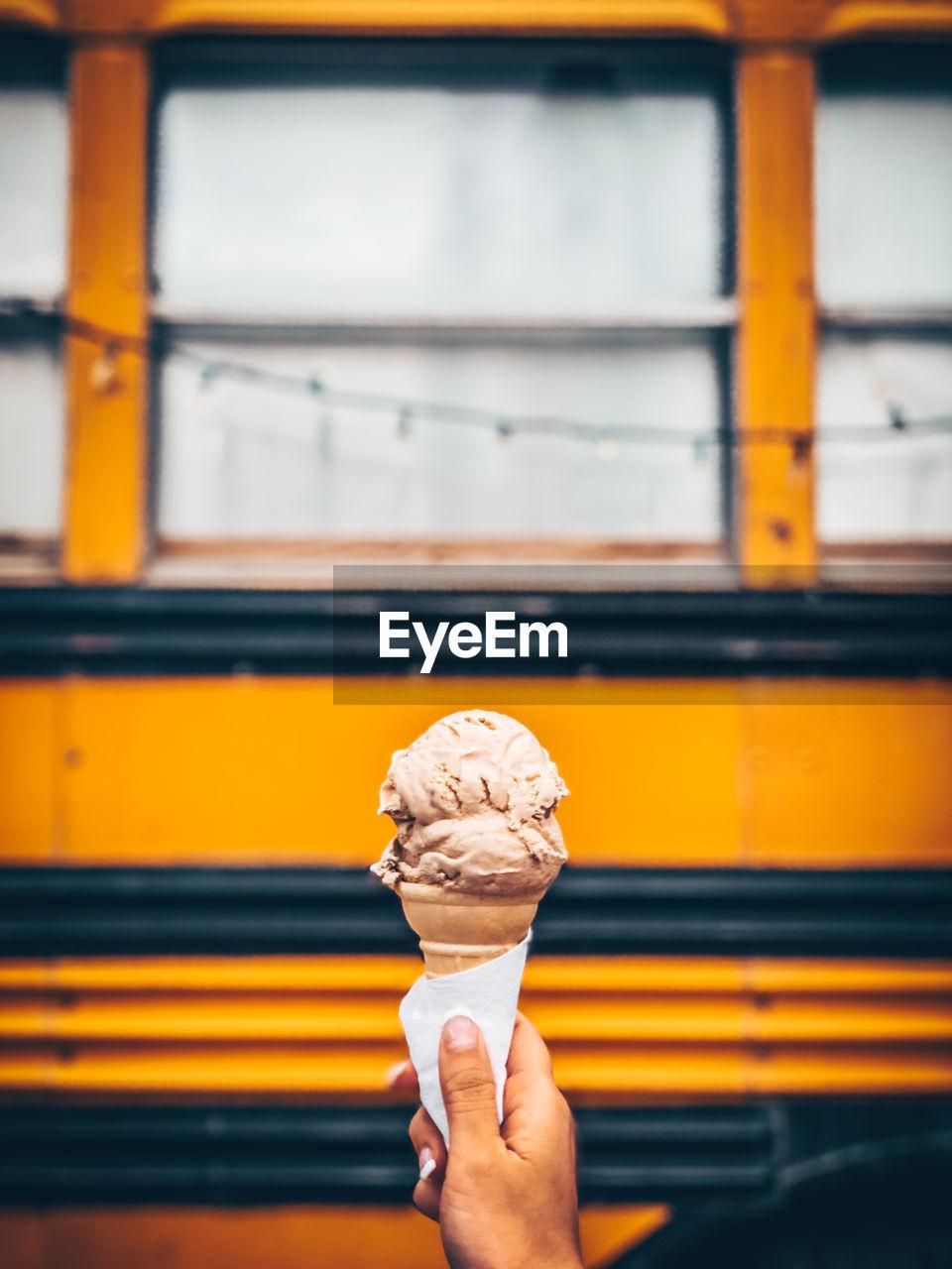 Human Hand Holding Ice Cream Against Bus