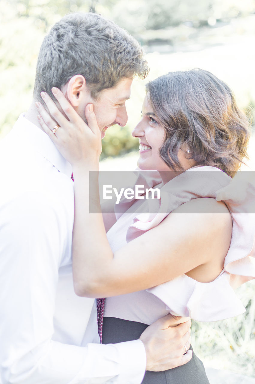 SIDE VIEW OF YOUNG COUPLE KISSING