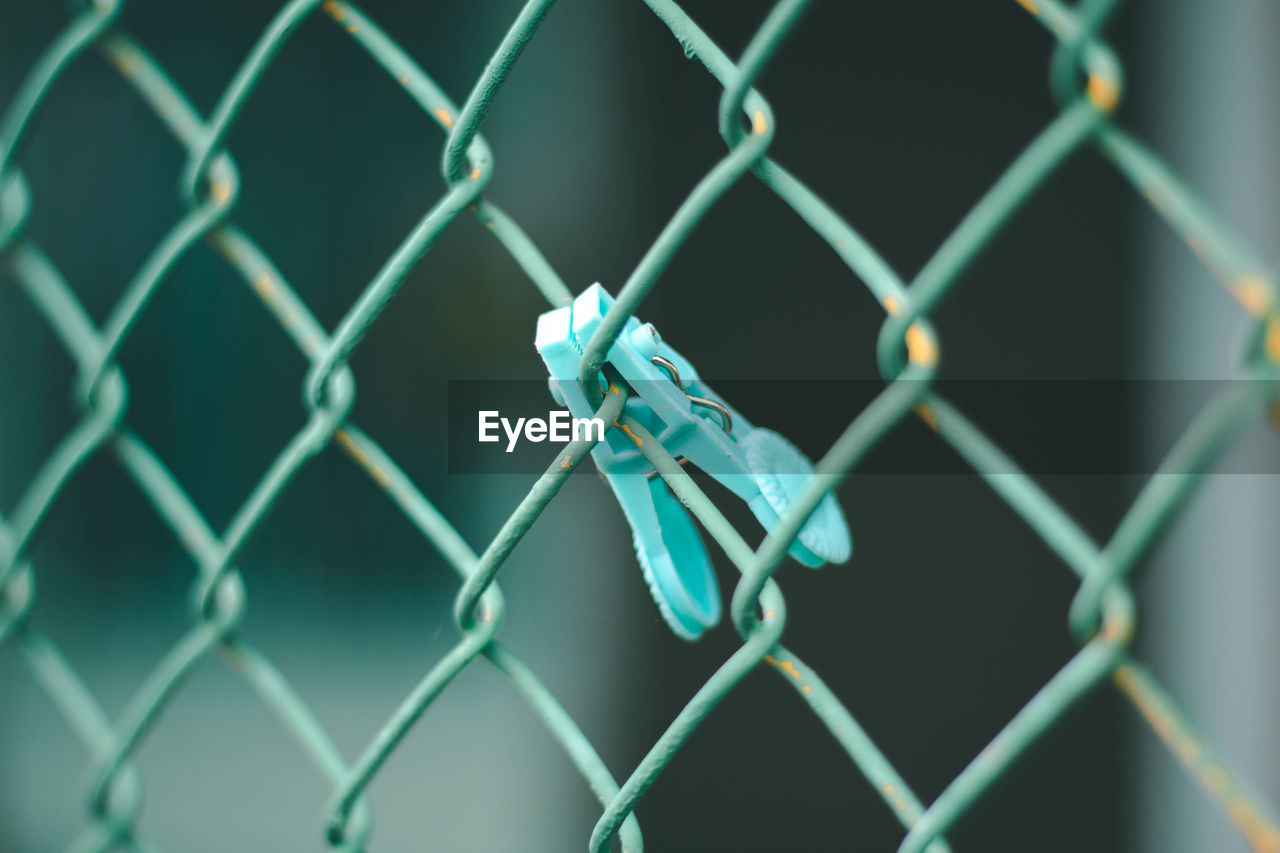 fence, chainlink fence, protection, security, boundary, barrier, metal, safety, close-up, no people, pattern, focus on foreground, blue, day, full frame, selective focus, nature, backgrounds, connection, outdoors, turquoise colored