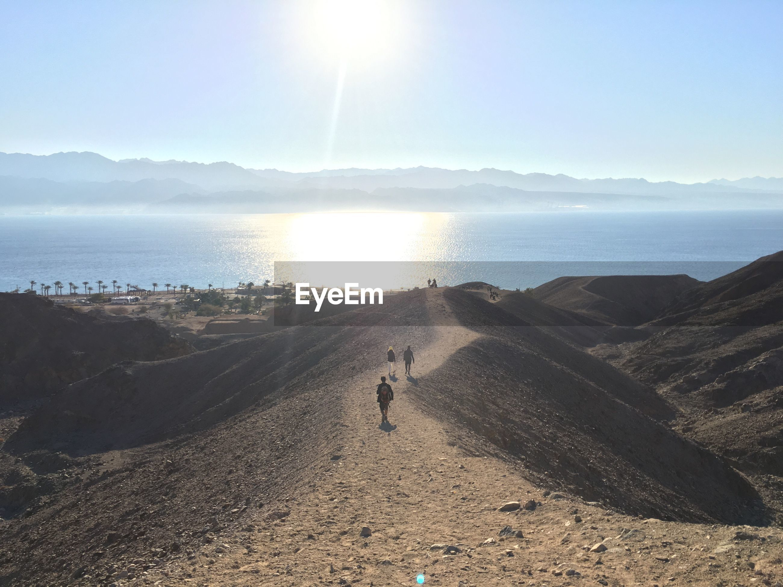 Distant view of people walking on landscape by sea against sky