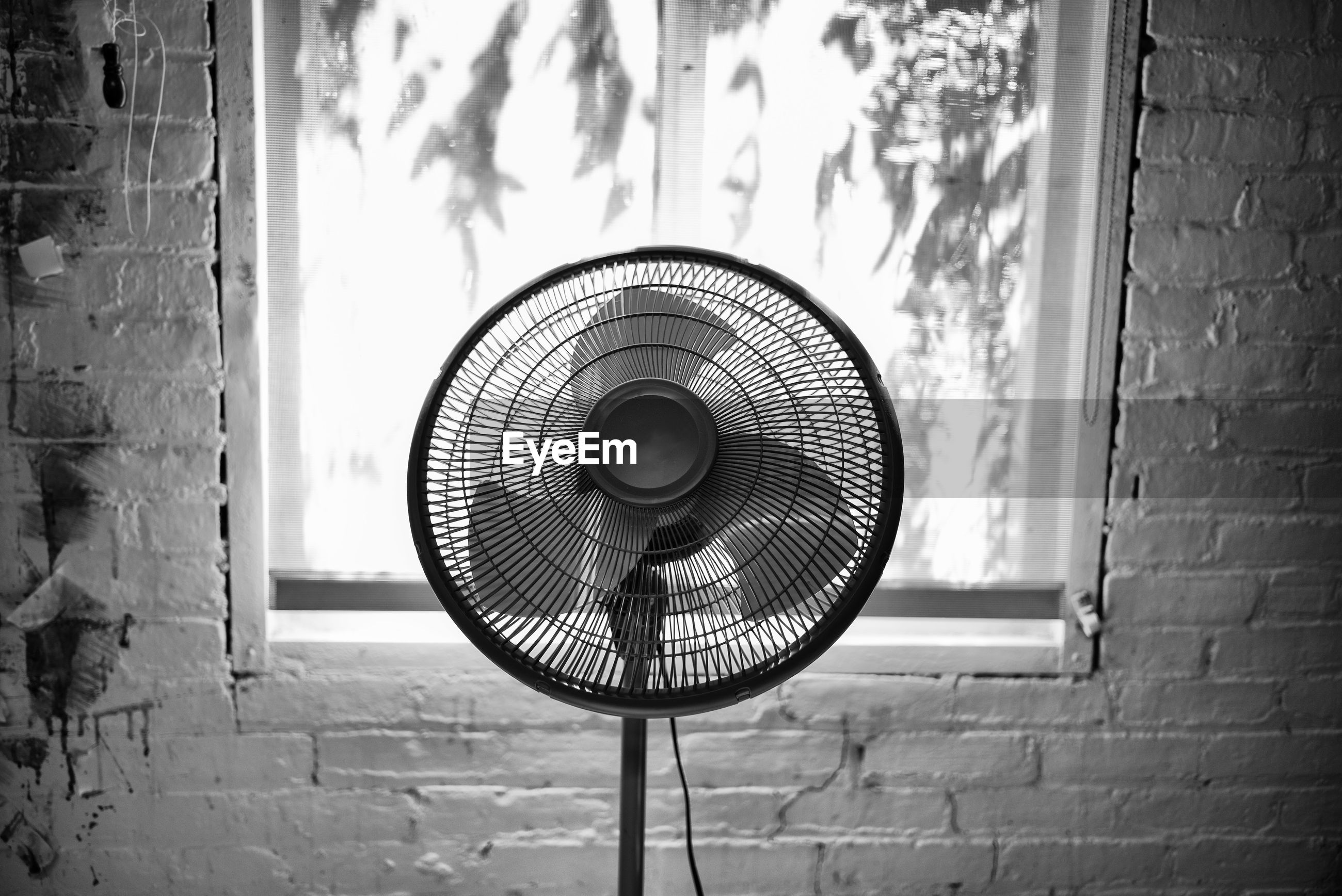 Fan inside a building in front of a window black and white