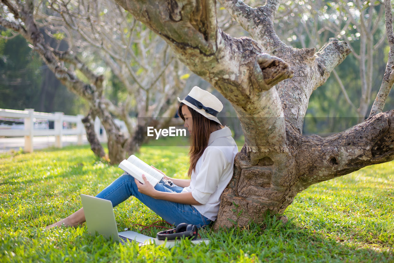 Side view of woman reading while sitting by tree trunk at park