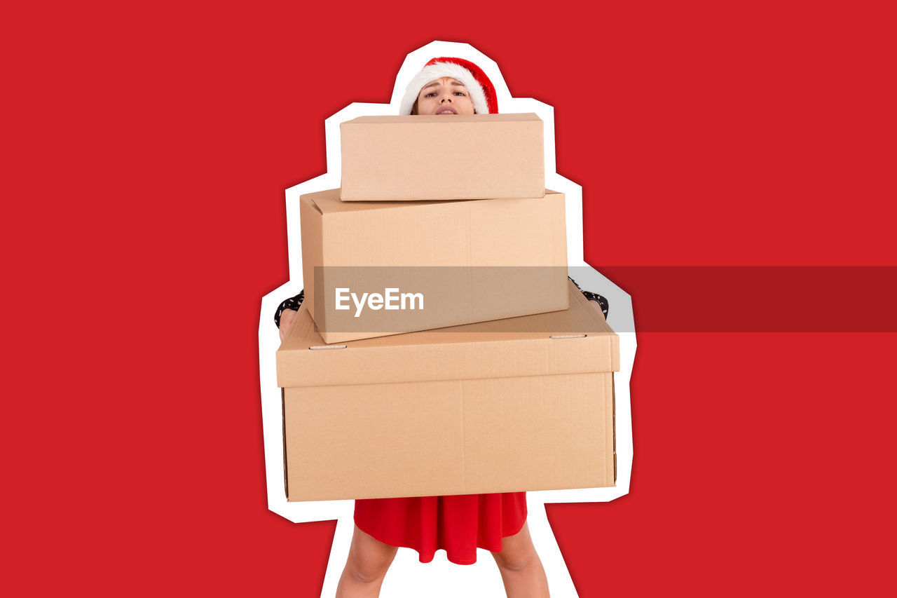 Portrait of shocked woman holding boxes against red background