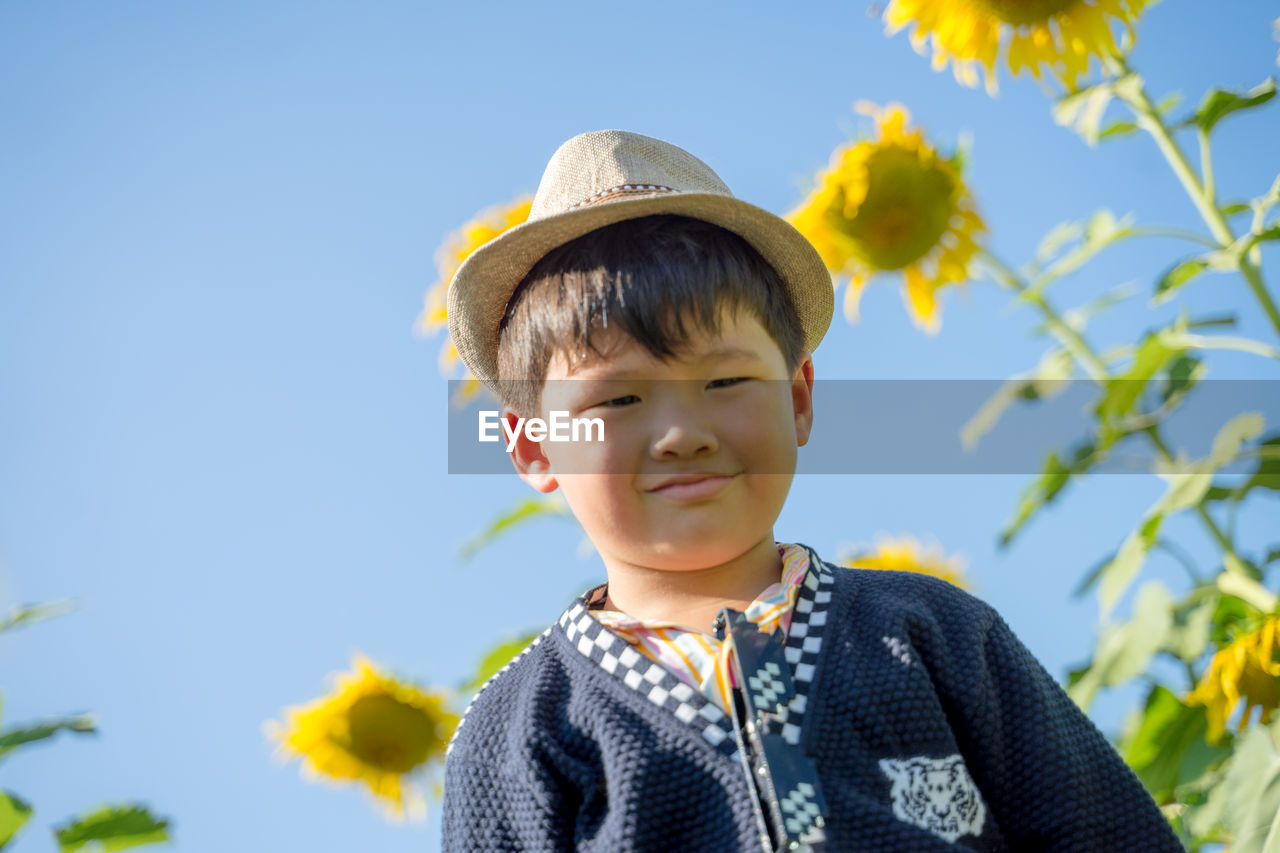 Portrait of cute smiling boy in hat against sky