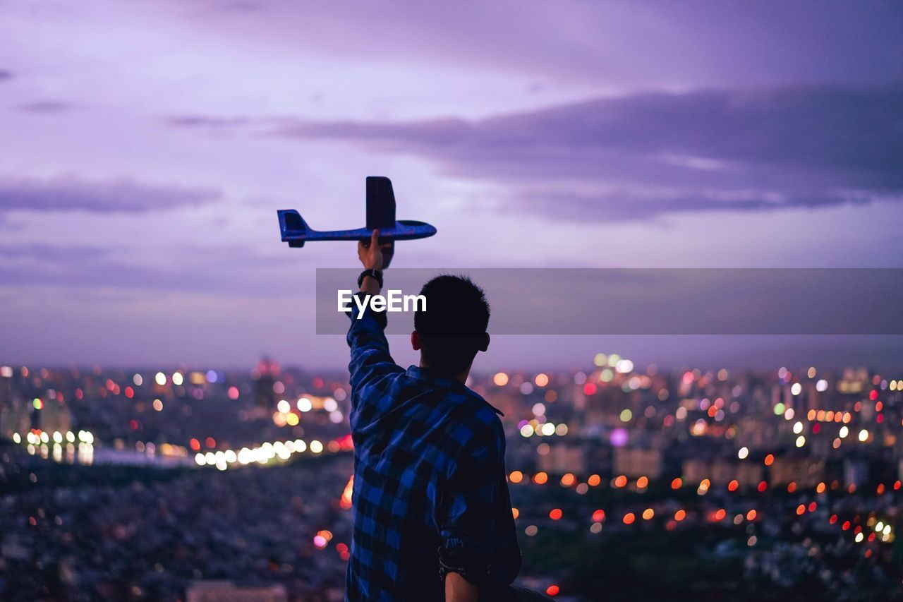 Rear view of man holding model airplane against illuminated cityscape at dusk
