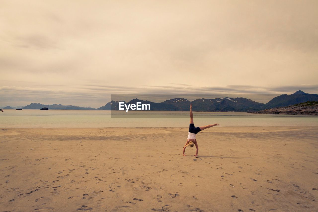 Woman Doing Handstand On Shore At Beach Against Sky