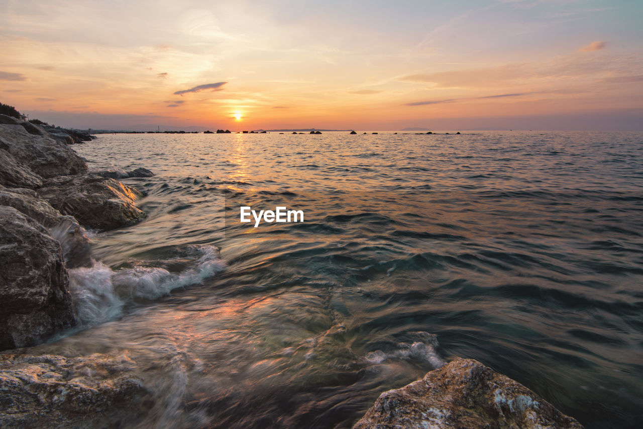 sunset, sea, beauty in nature, scenics, water, nature, sky, horizon over water, rock - object, tranquil scene, tranquility, cloud - sky, sun, idyllic, outdoors, no people, wave, beach, day