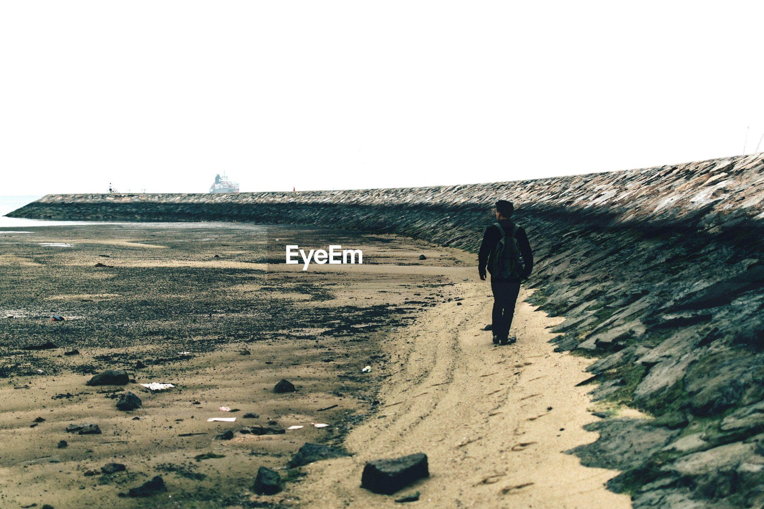 Full length of man walking at beach against clear sky