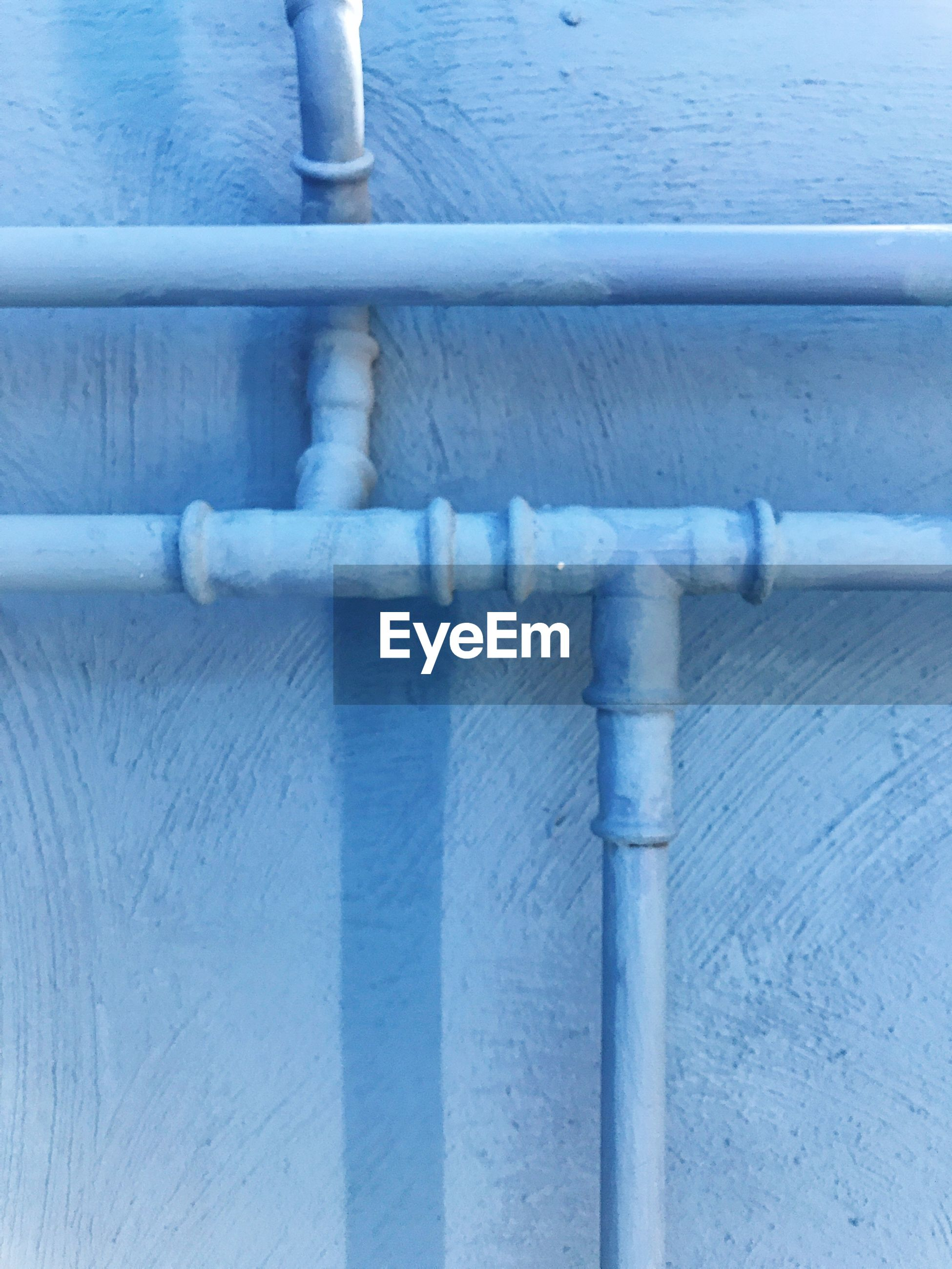 Close-up of pipeline on blue colored wall