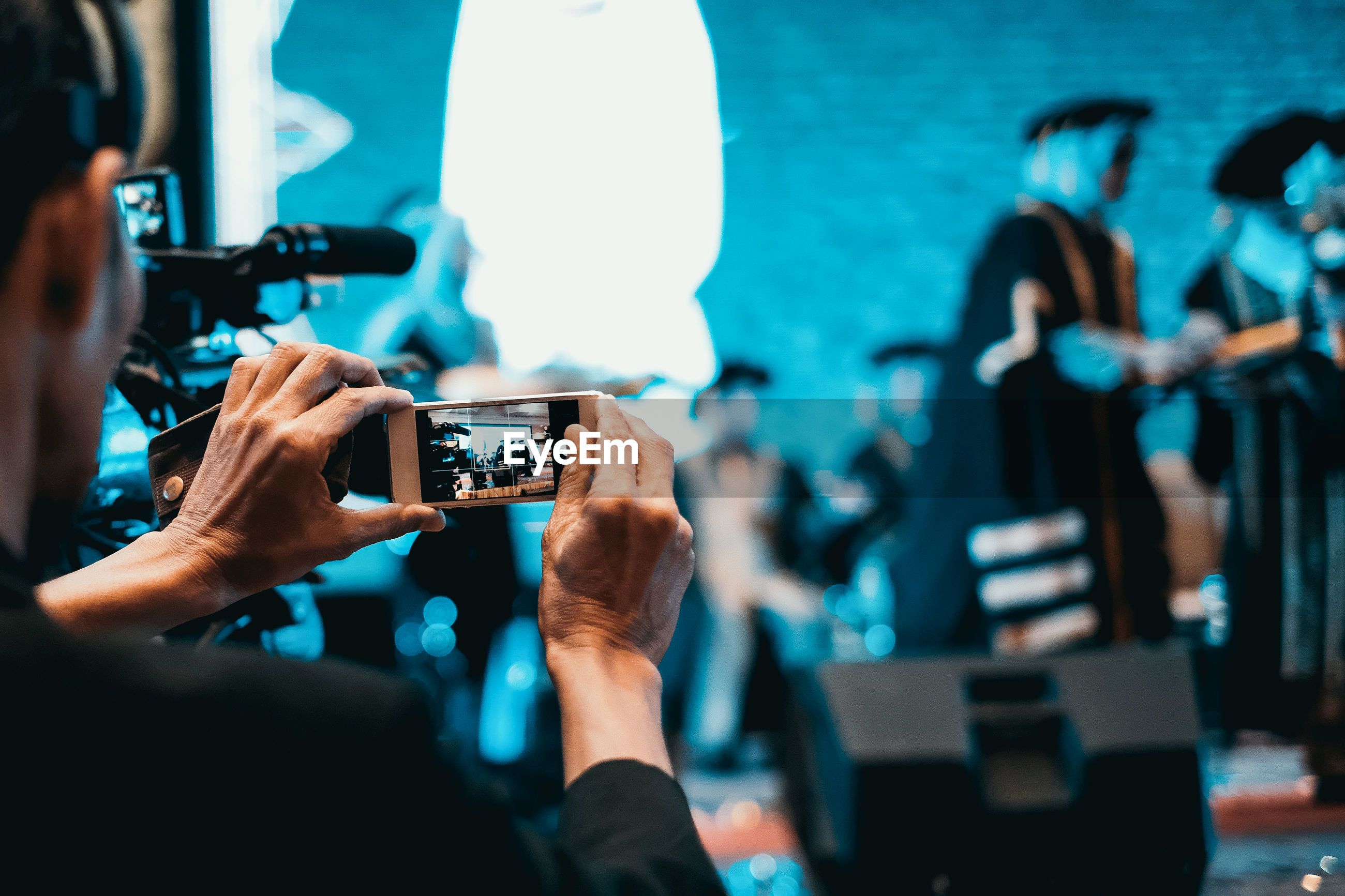 Rear view of person filming through smart phone during graduation ceremony