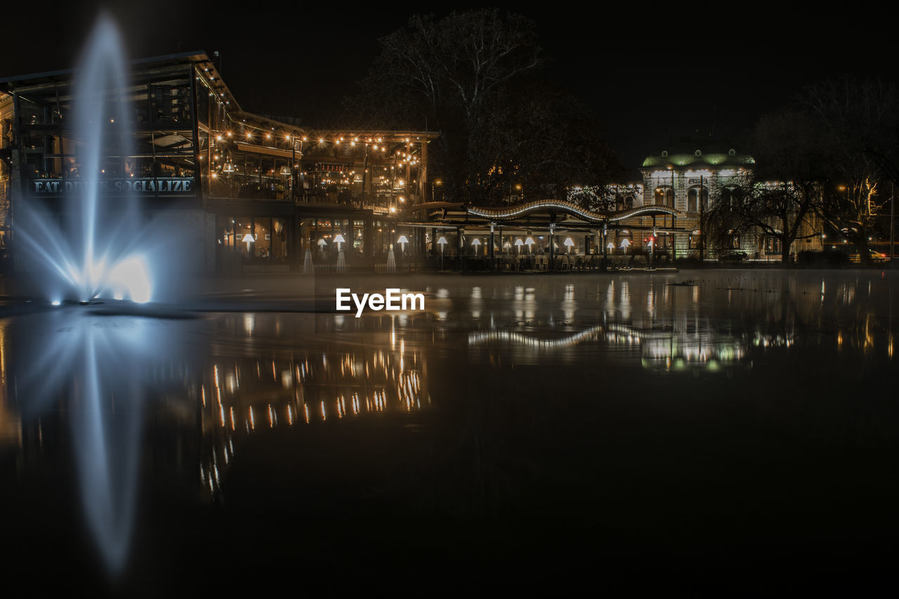 reflection, illuminated, night, water, architecture, built structure, building exterior, waterfront, tree, no people, nature, building, city, river, glowing, plant, residential district, outdoors, nightlife