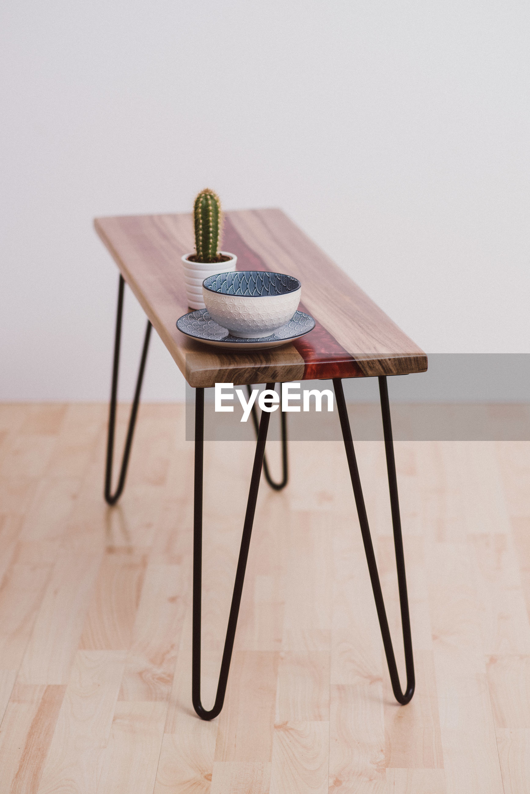 High angle view of crockery and potted plant on table against wall