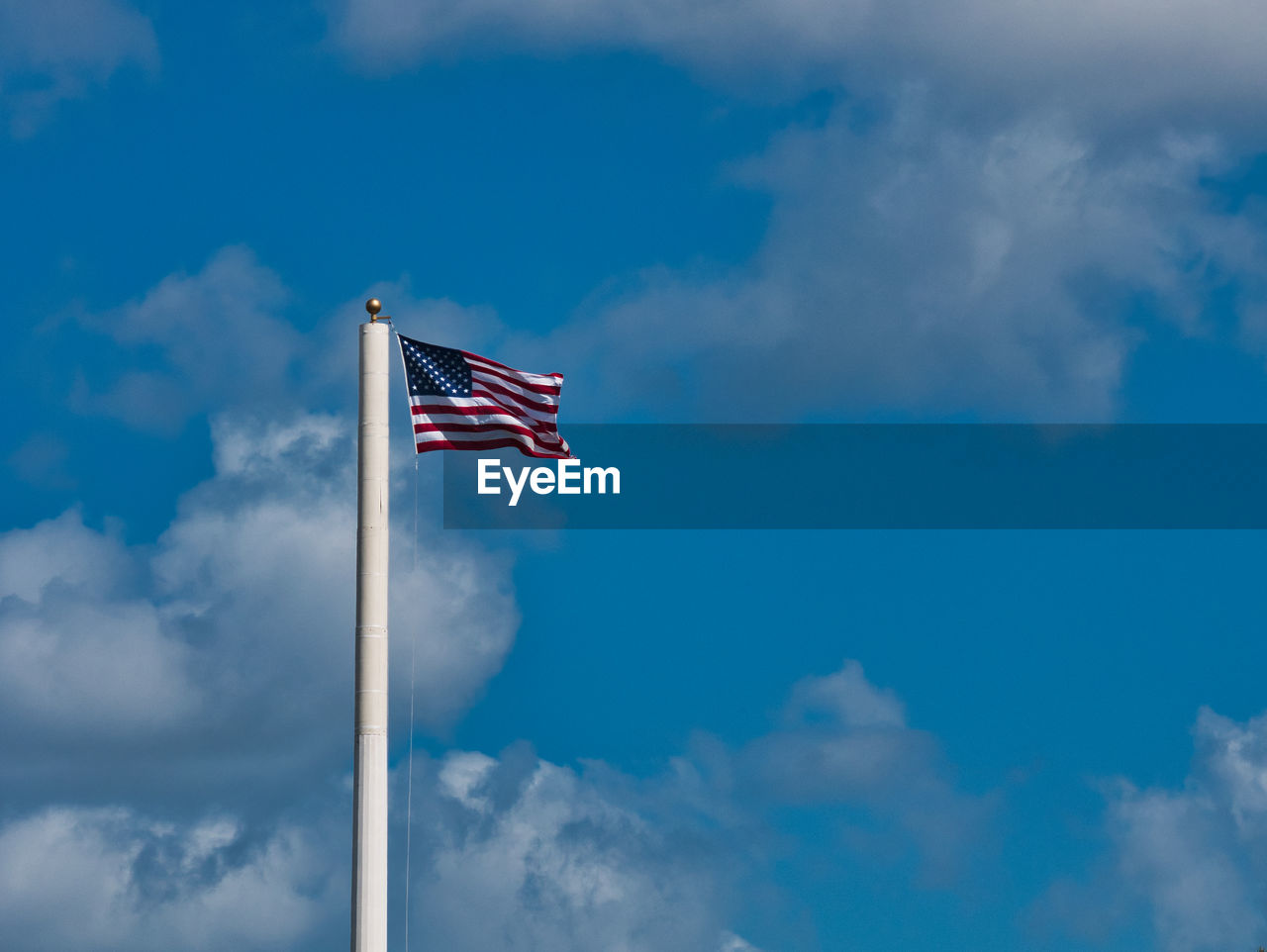 cloud - sky, patriotism, sky, low angle view, flag, blue, striped, nature, environment, no people, day, wind, pole, pride, outdoors, waving, independence, national icon, plane
