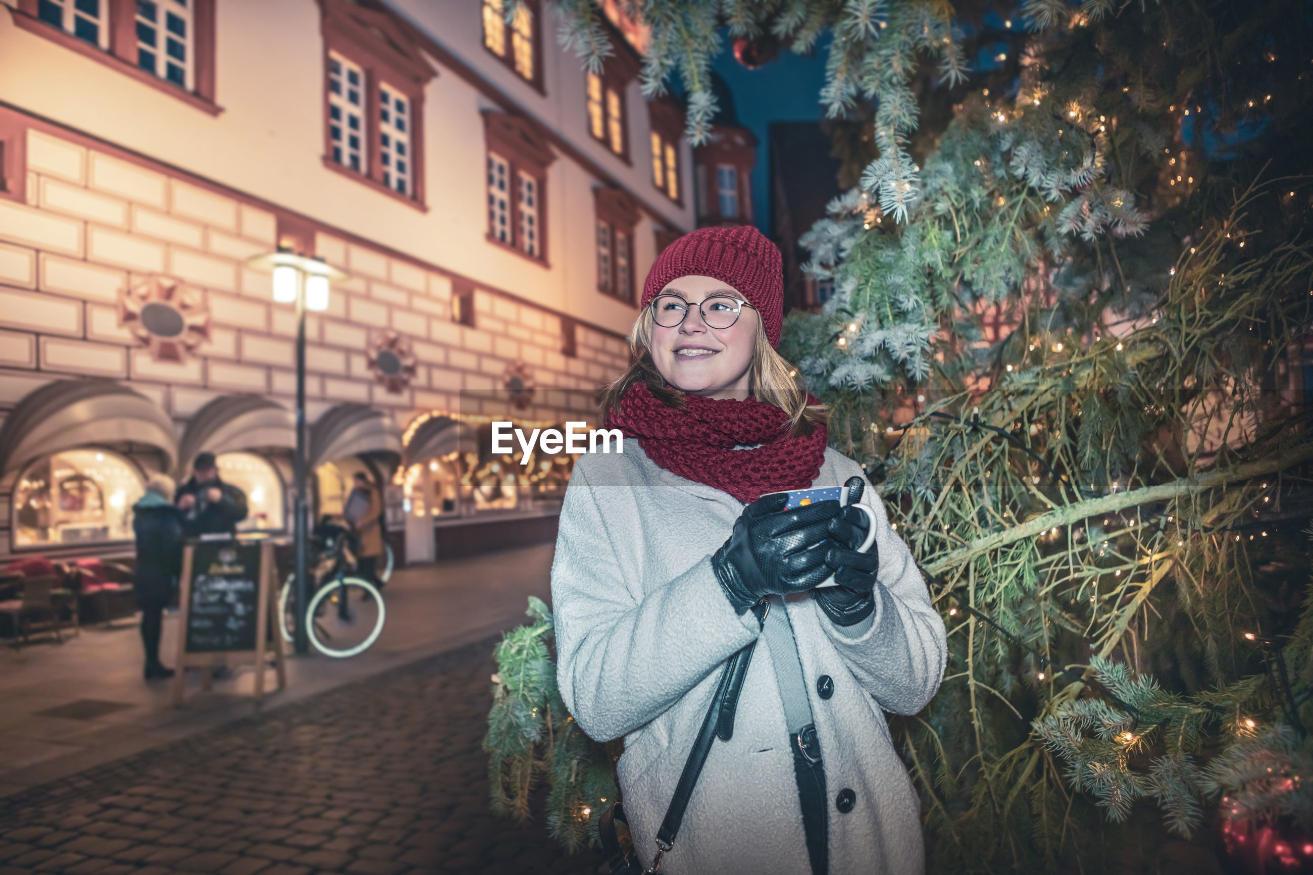 Smiling young woman standing in city at night