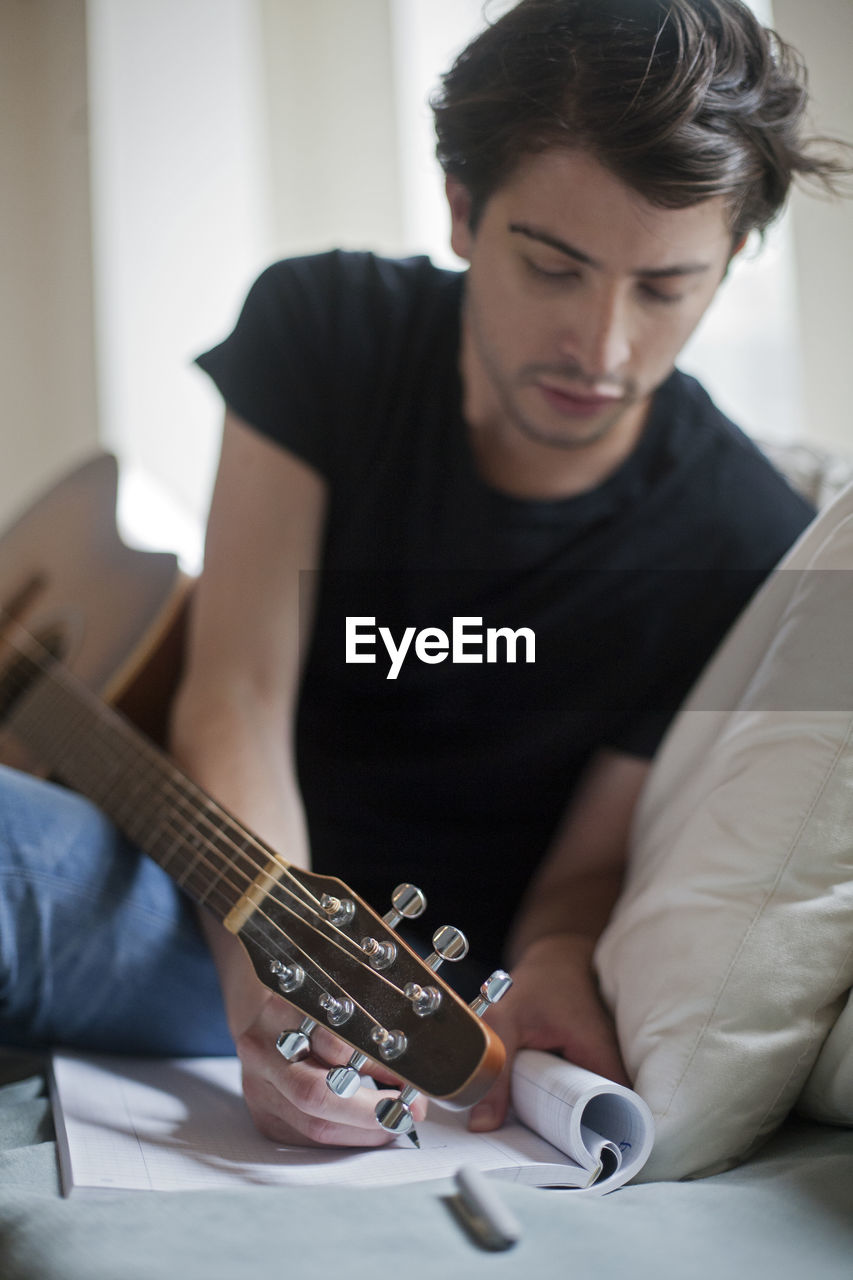 MIDSECTION OF MAN PLAYING GUITAR IN THE ROOM