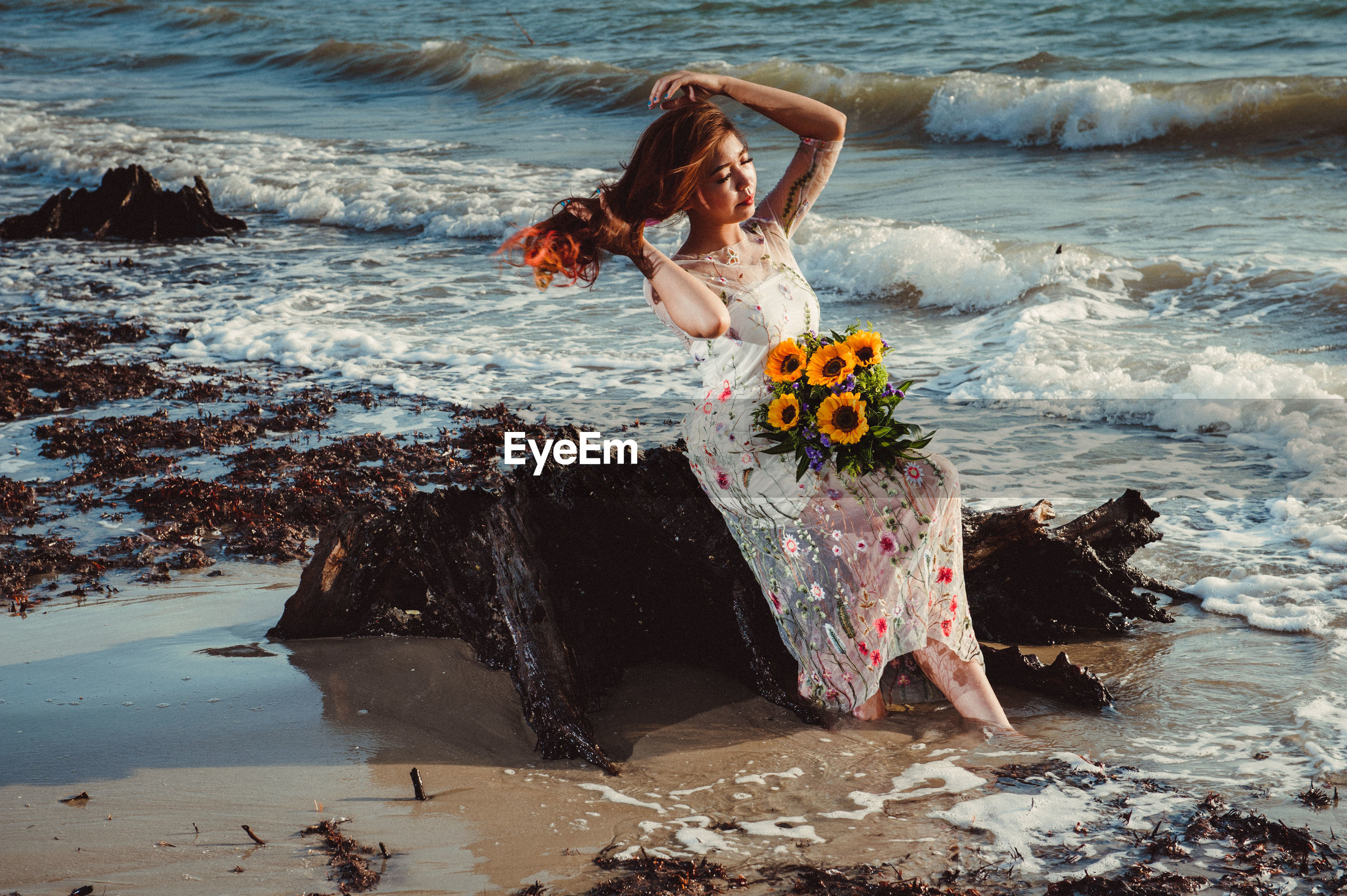 Full length of woman with flowers sitting on rock at sea shore against sky