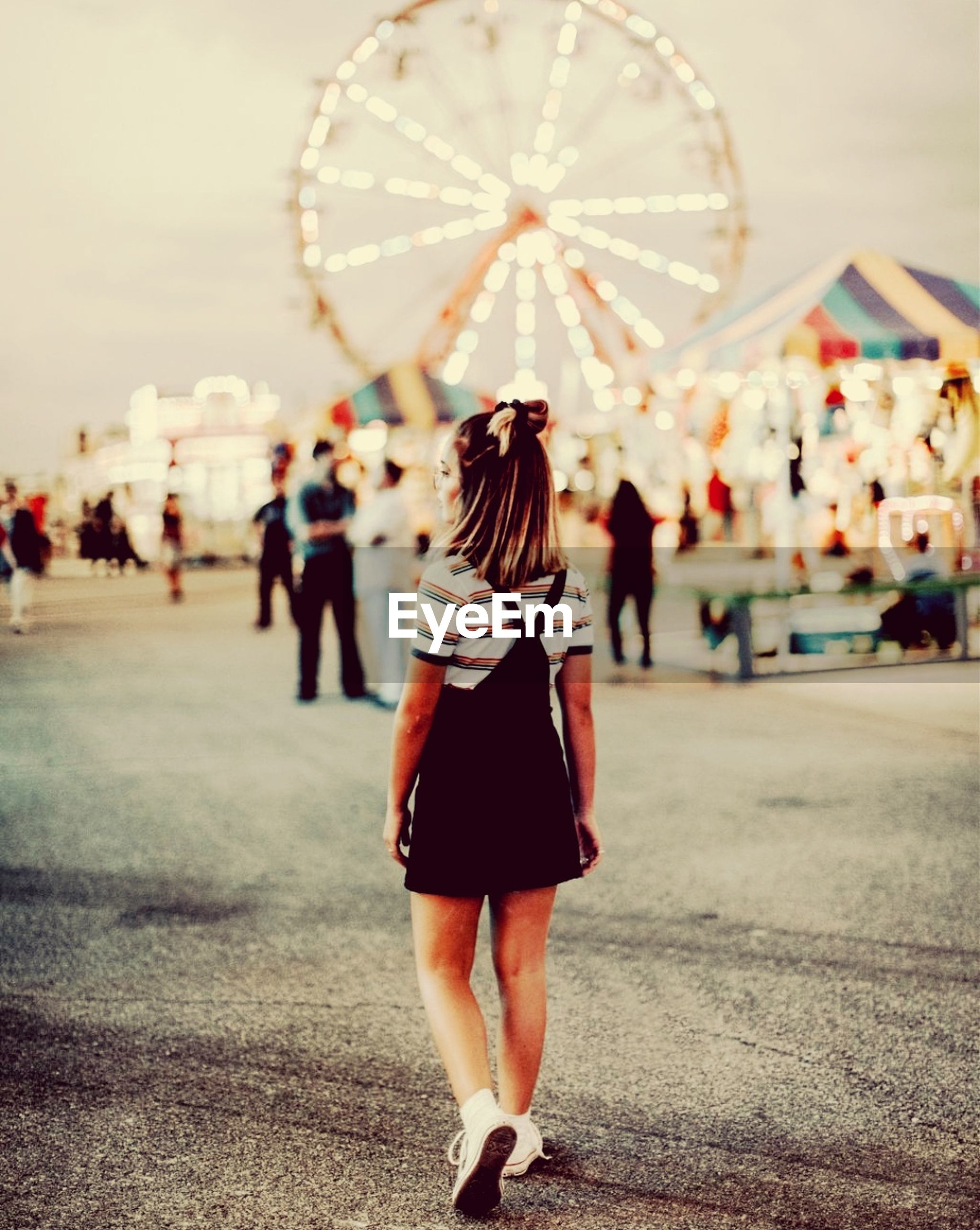 rear view, real people, full length, one person, focus on foreground, women, adult, leisure activity, lifestyles, incidental people, city, walking, amusement park, street, standing, amusement park ride, arts culture and entertainment, ferris wheel, day, hairstyle, shorts